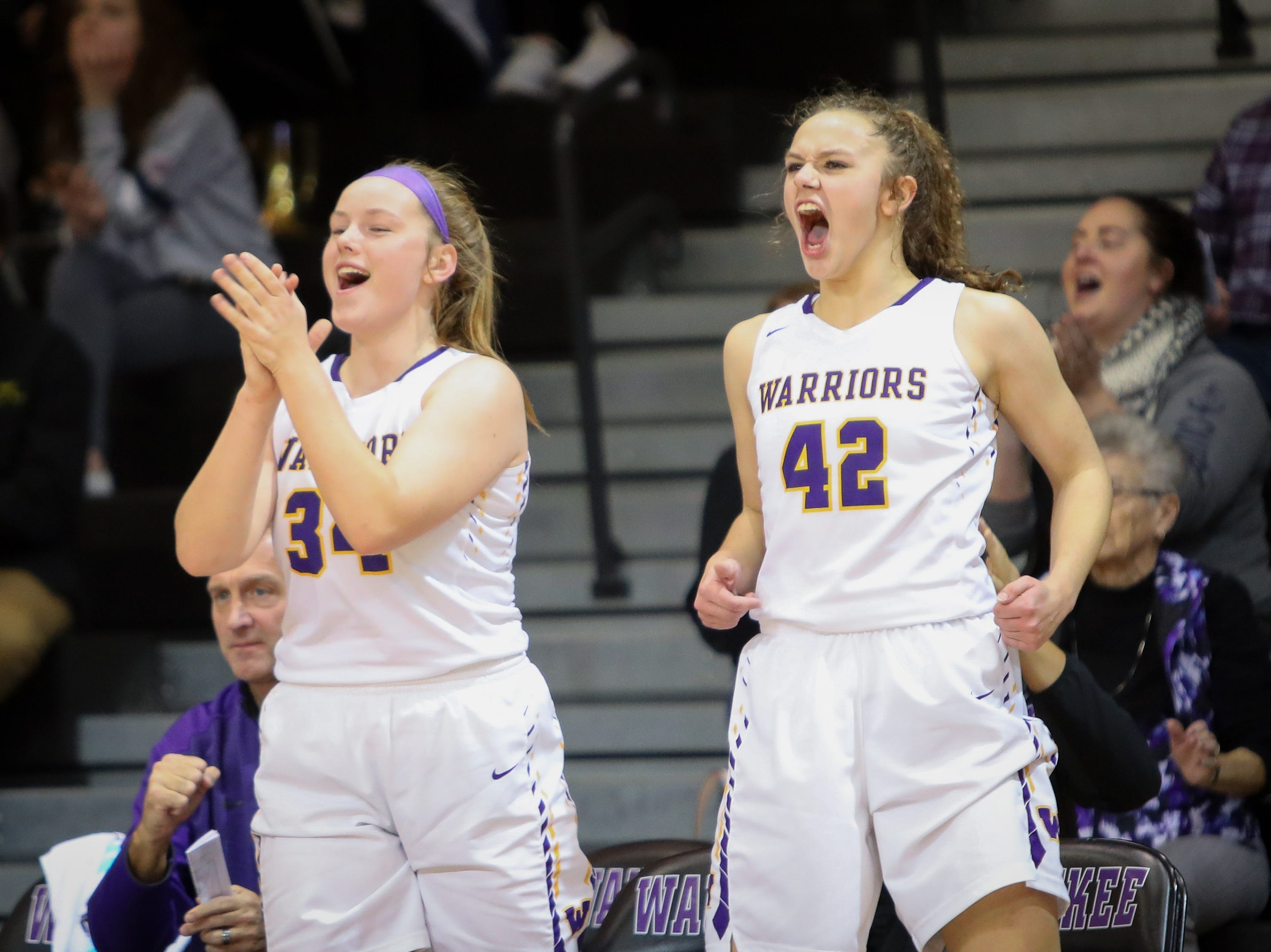 Waukee sophomores Megan Earney and Taryn Reitsma cheer on their teammates during a girls high school basketball game between the Valley Tigers and the Waukee Warriors at Waukee High School on Dec. 14, 2018 in Waukee, Iowa.