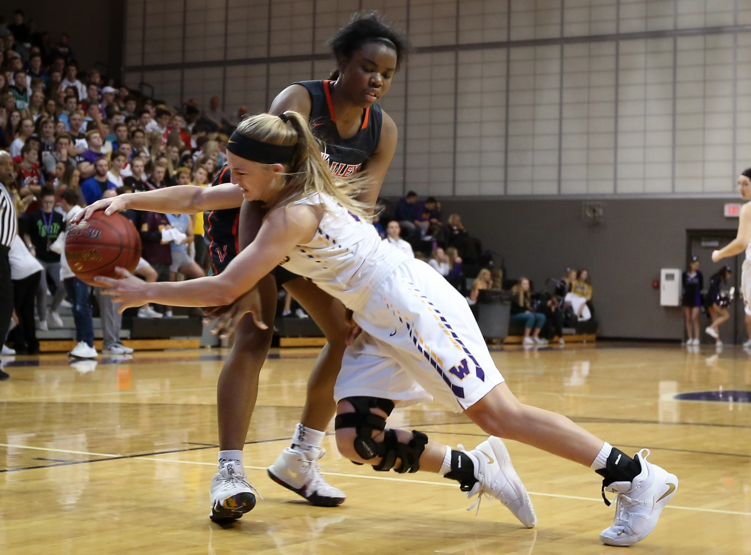 Waukee sophomore Katie Dinnebier pass the ball around Valley senior Zoe Young during a girls high school basketball game between the Valley Tigers and the Waukee Warriors at Waukee High School on Dec. 14, 2018 in Waukee, Iowa.