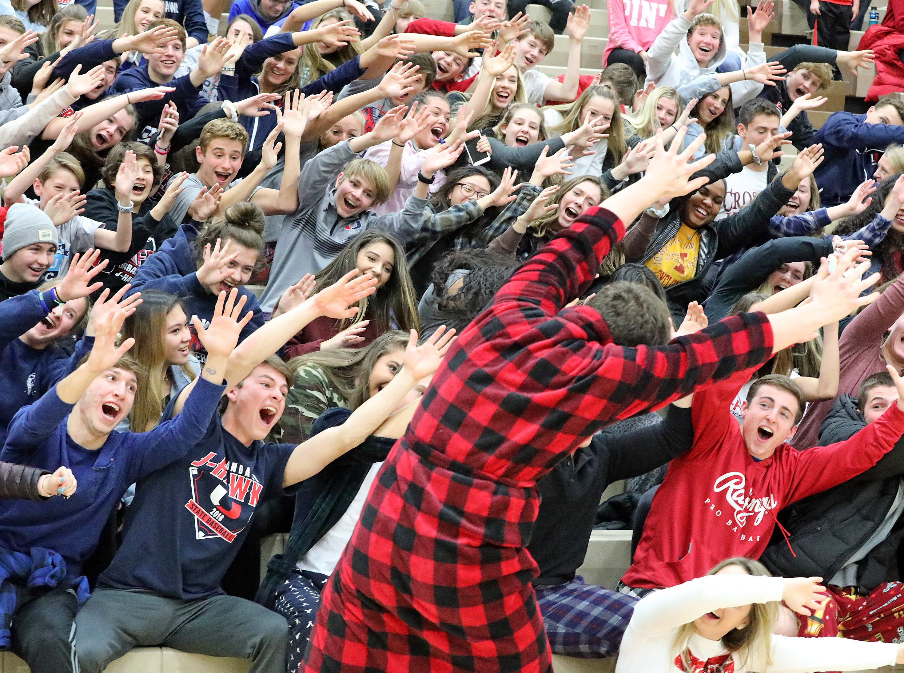 Urbandale senior Evan Smith and his red flannel bath robe fire up the students to the left as the Ankeny Hawks compete against the Urbandale J-Hawks in high school basketball on Friday, Dec. 14, 2018 at Urbandale High School. Ankeny won 62 to 52 to remain undefeated at 6-0.