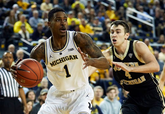 Michigan guard Charles Matthews dribbles, defended by Western Michigan guard Jared Printy in the first half on Saturday, Dec. 15, 2018, at Crisler Center.