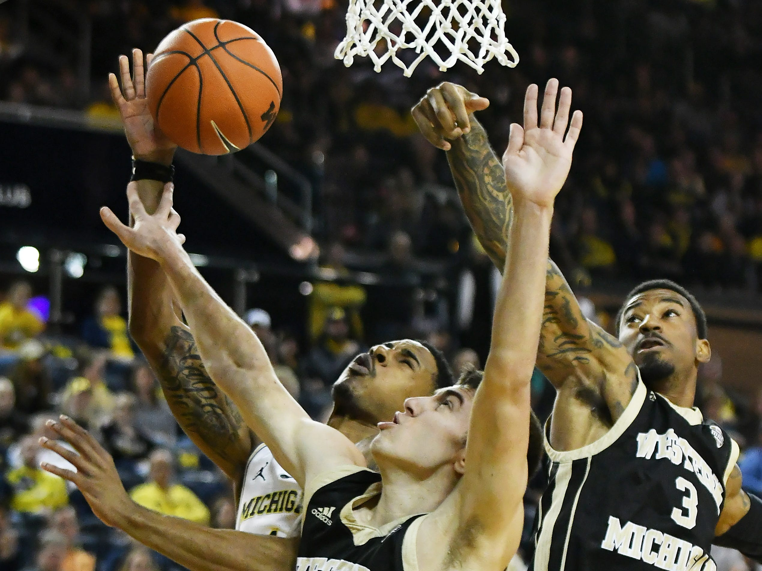 Western Michigan guard Jared Printy (4) and Western Michigan guard Josh Davis (3) converge on Michigan guard Charles Matthews (1) going to the basket in the first half as Michigan wins 70-62 over Western Michigan at Crisler Center in Ann Arbor, Mich. on Dec. 15, 2018.