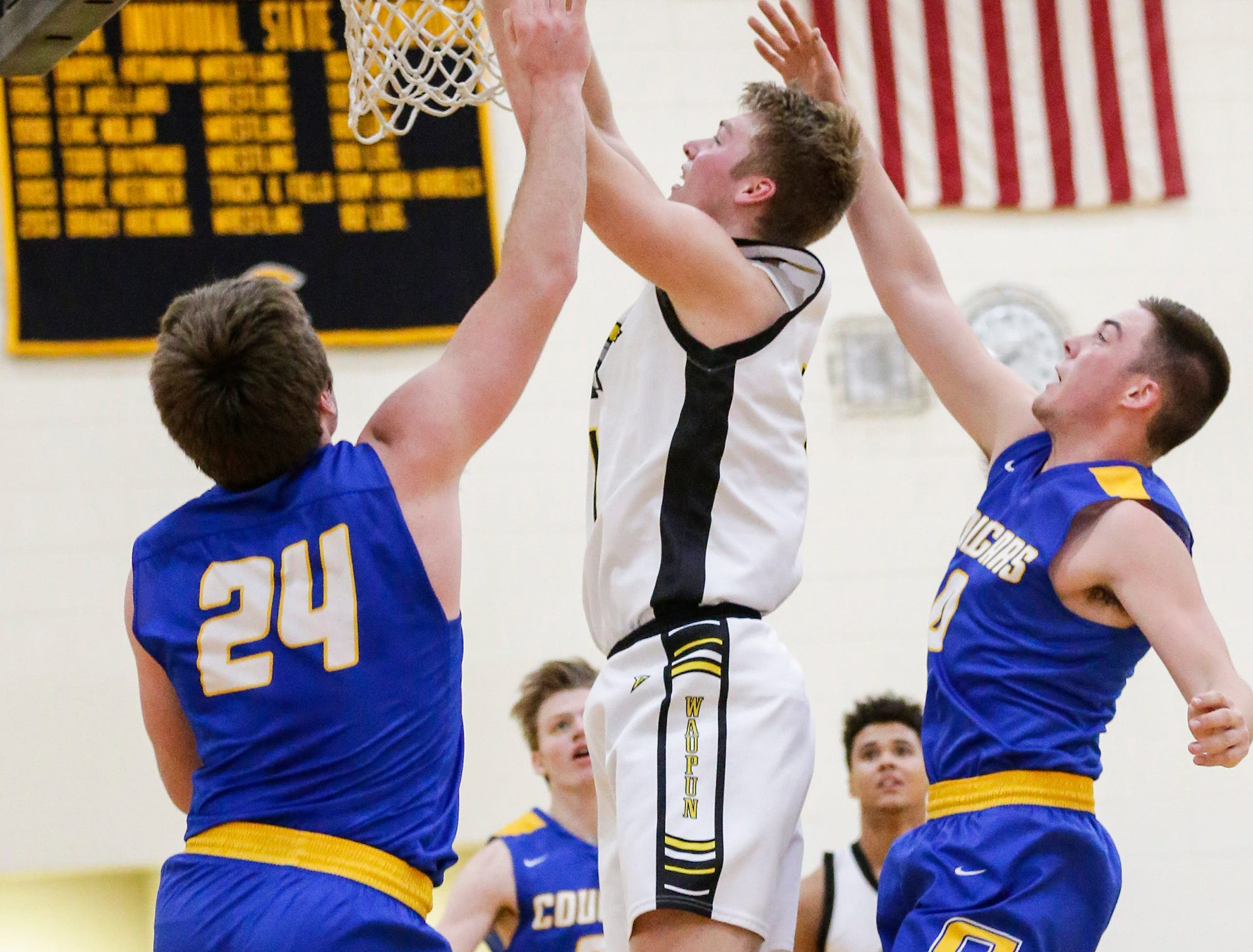 Waupun High School boys basketball's Marcus Domask goes up for a basket between Campbellsport High School's Nicholas Narges and Kade Walsh during their game Friday, December 14, 2018 in Waupun. Waupun won the game 64-33. Doug Raflik/USA TODAY NETWORK-Wisconsin