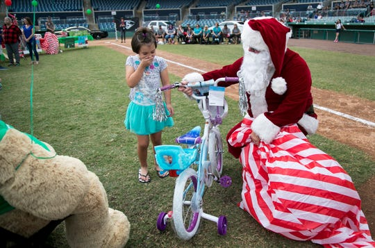 Dylani Koelber, 6, reacts to her new bike at the Florida Highway Patrol's Adopt-A-Family Christmas event on Saturday at City of Palms Park in Fort Myers. Dylani's mom and sisters were honored along with the family of fallen Fort Myers Police Officer Adam Jobbers-Miller. Dylani's father Bruce Koelber was killed by a drunk driver in August.