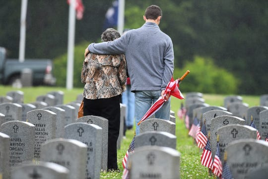 "Family members of fallen veterans visit the graves at M.J. ""Dolly"" Cooper Veterans Cemetery after a Memorial Day service Monday, May 28, 2018. 