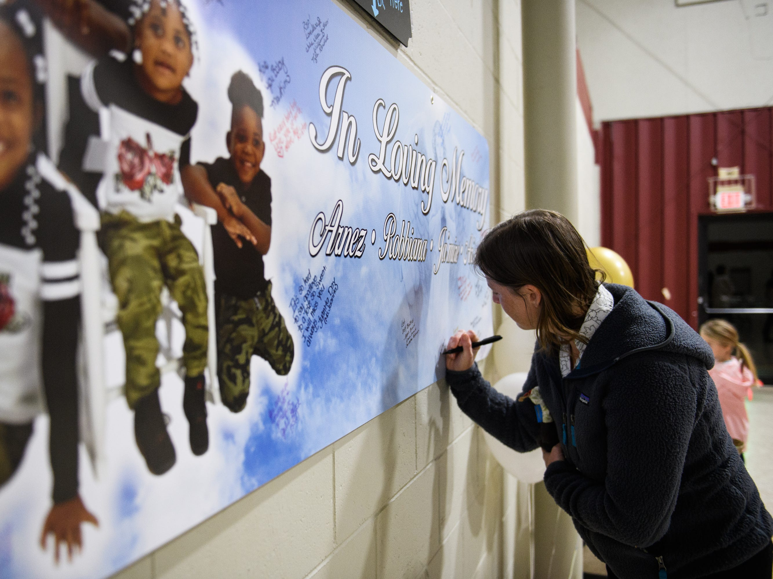 Lauren Schmaltz signs a poster for the four siblings who died due to a single-vehicle DUI wreck during a vigil held in their honor at Clearview Baptist Church on Friday, Dec. 14, 2018.