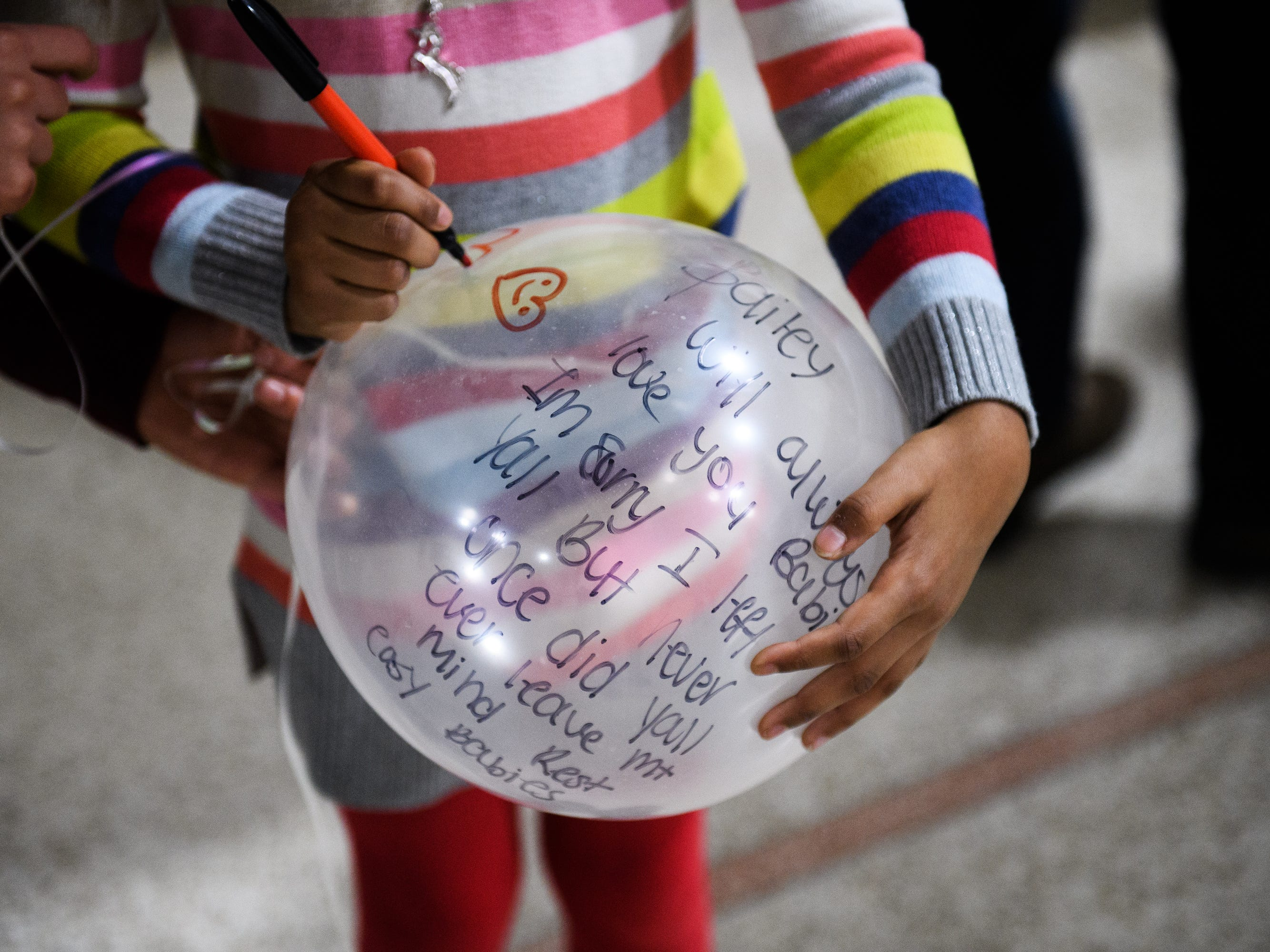 Many Lofton, 6, writes a message on a balloon during a vigil for siblings Arnez Yaron Jamison, Jr., 4, Robbiana Evans, 6, Jamire Halley, 8, and Ar'mani Jamison, 2, at Clearview Baptist Church on Friday, Dec. 14, 2018.