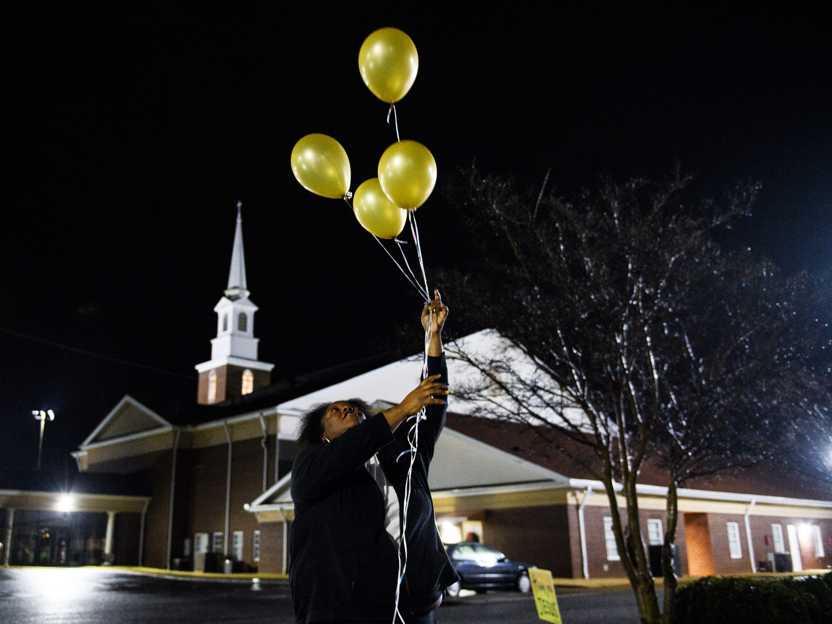 Jacqueline Brown releases balloons during a vigil at Clearview Baptist Church in honor of her four children on Friday, Dec. 14, 2018.