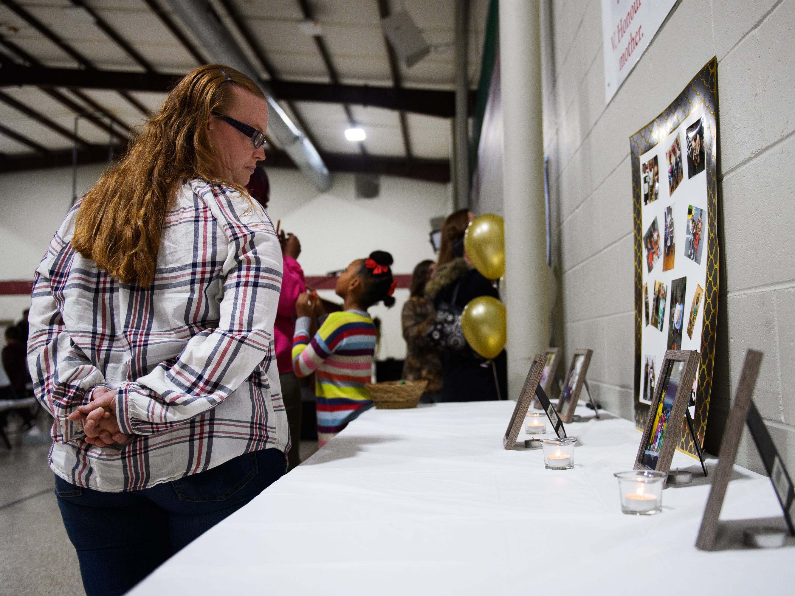Jamie Read looks at images of siblings Arnez Yaron Jamison, Jr., 4, Robbiana Evans, 6, Jamire Halley, 8, and Ar'mani Jamison, 2, during a vigil at Clearview Baptist Church on Friday, Dec. 14, 2018.
