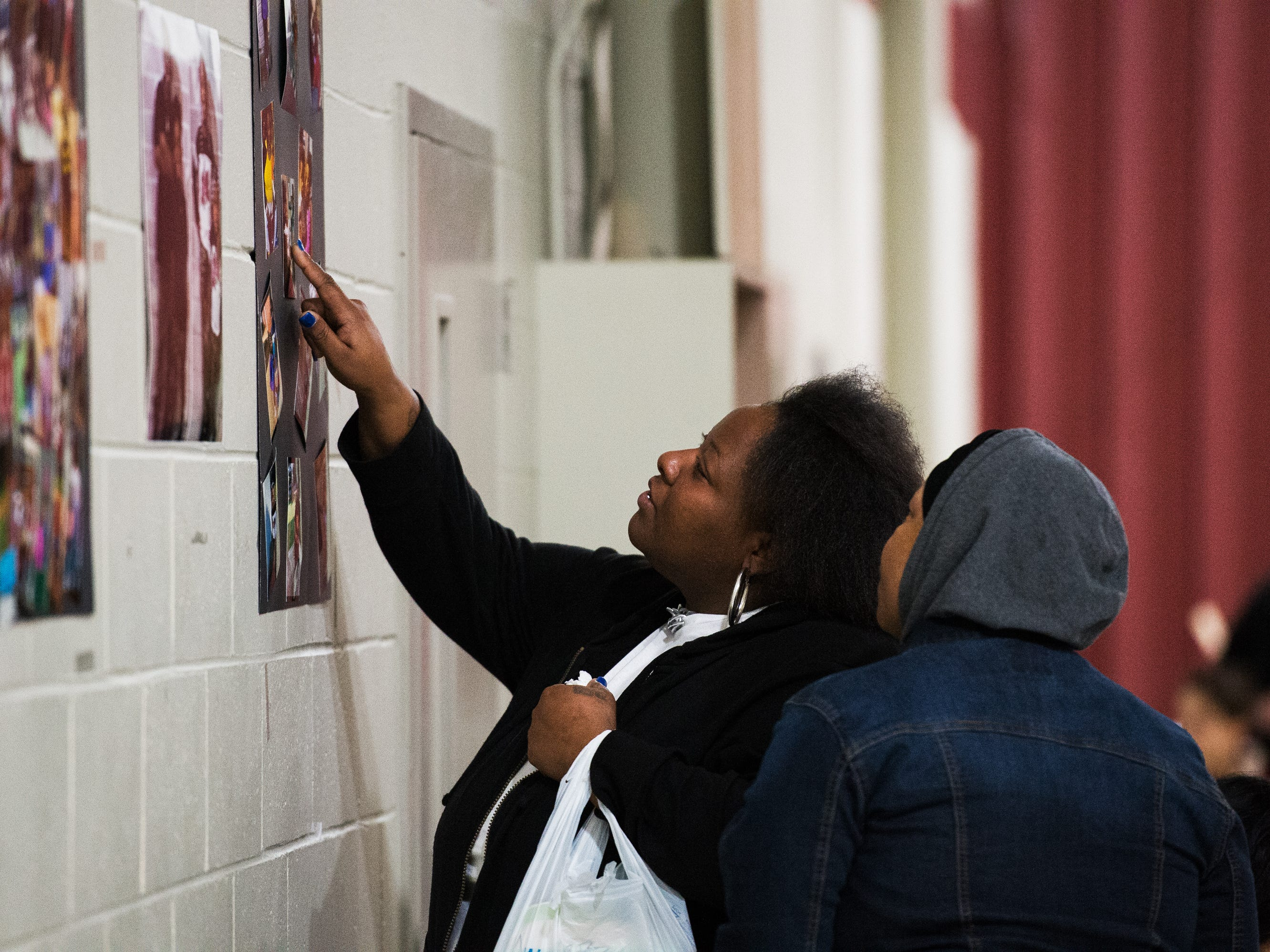 Jacqueline Brown looks at photographs of her children during vigil held in their honor at Clearview Baptist Church on Friday, Dec. 14, 2018.