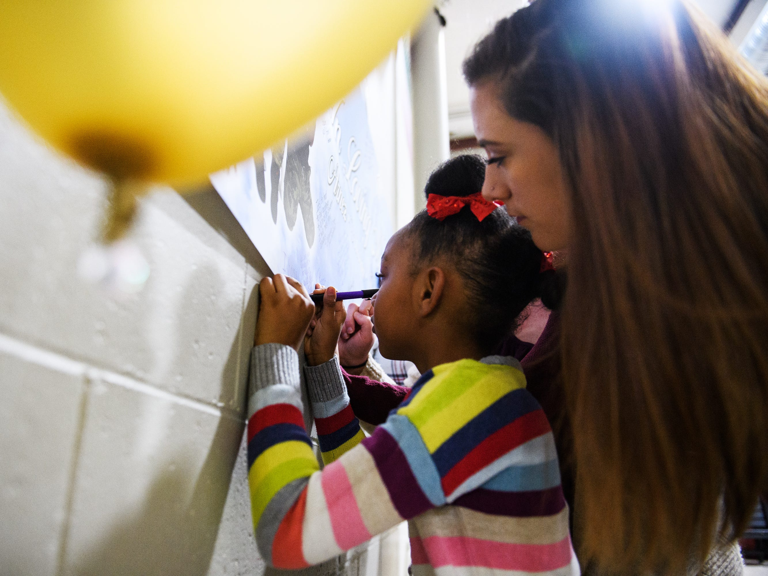 Many Lofton, 6, is held by Bailey Tatham as she signs a poster for the four siblings who died due to a single-vehicle DUI wreck during a vigil held in their honor at Clearview Baptist Church on Friday, Dec. 14, 2018.