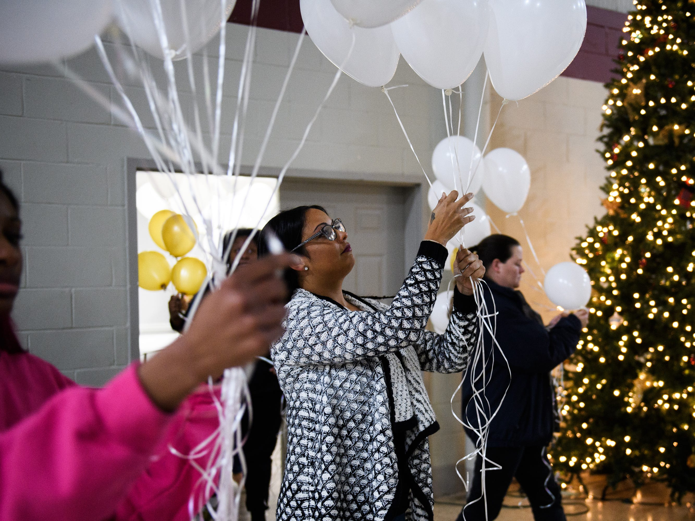 Vanessa Brown and others hold balloons during a vigil for the four siblings who died due to a single-vehicle DUI wreck at Clearview Baptist Church on Friday, Dec. 14, 2018.
