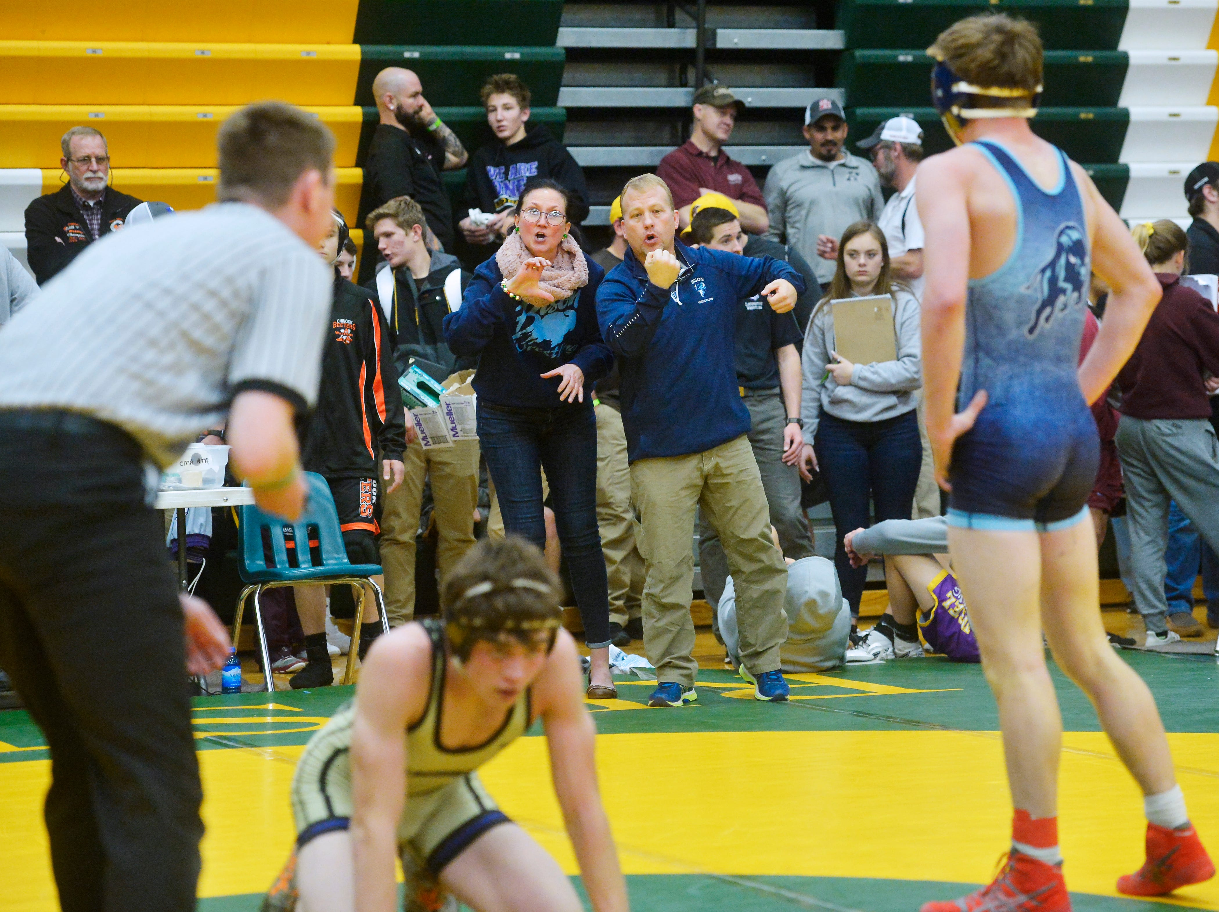 Great Falls High coach Steve Komac relays instructions to his wrestler, Trevin Smith, through sign language interpreter Sandra VanTighem, left,  during the CMR Holiday Classic Wrestling Tournament in the CMR Fieldhouse on Friday.