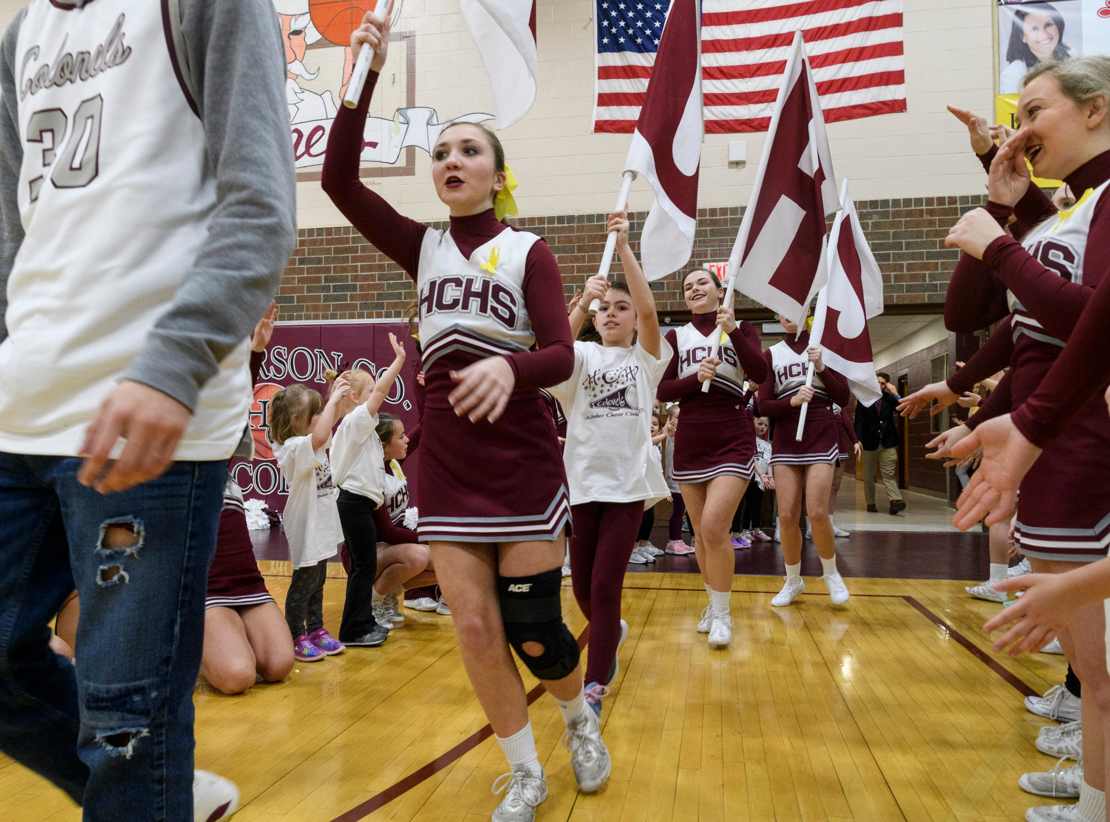 The Henderson County cheerleaders follow behind the boys basketball team as they rush the court before the start of the game against the Christian County Colonels at Henderson County High School in Henderson, Ky., Friday, Dec. 14, 2018. Christian County defeated Henderson County 79-71.