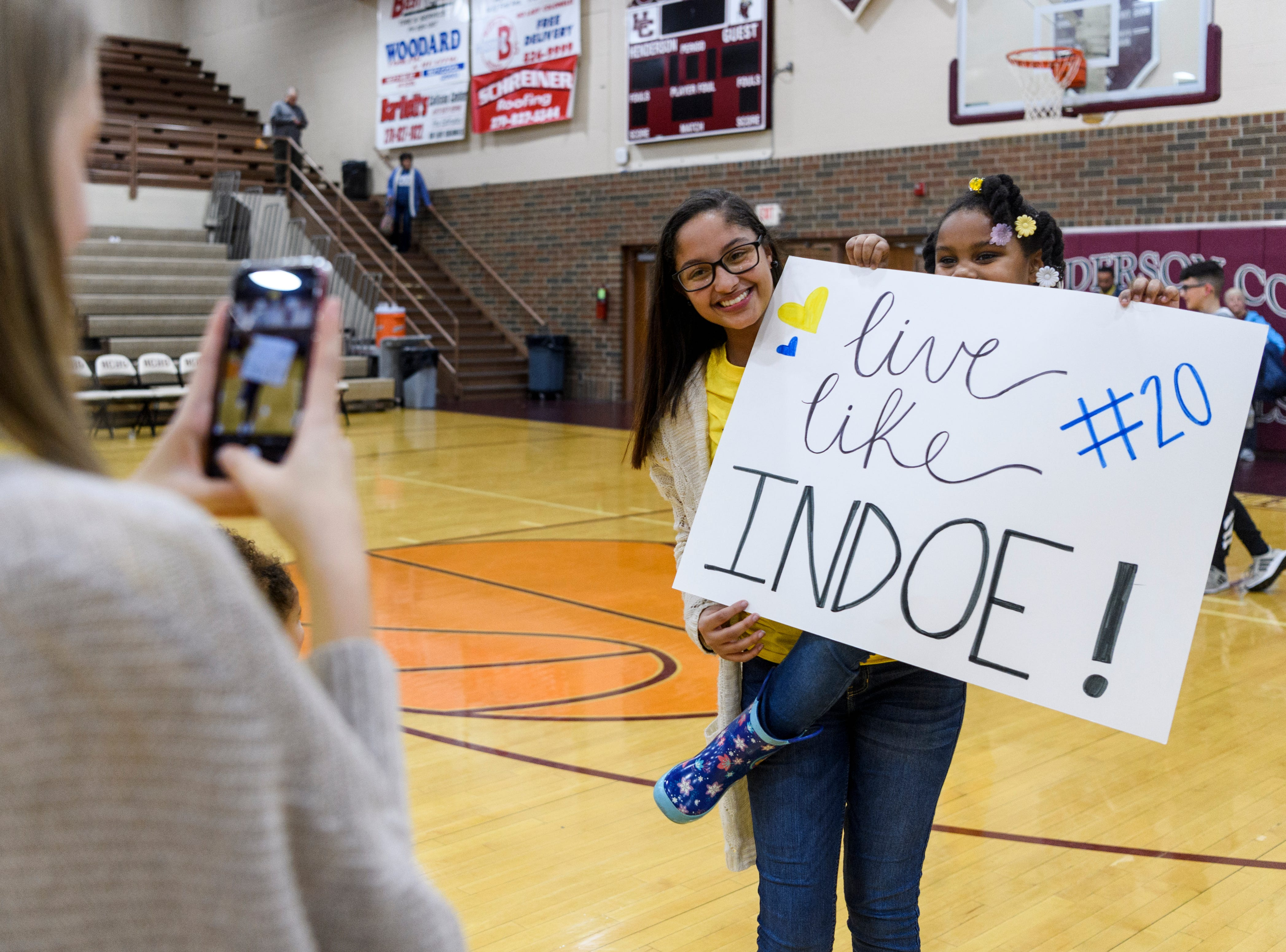 Innasent Walker, 6, poses for a picture with a Henderson County high school student after the Christian County Colonels vs Henderson County Colonels basketball game in Henderson, Ky., Friday, Dec. 14, 2018. The sign they were holding was made in honor of InDarius Walker, a Henderson County junior who died last Monday after battling bone cancer.