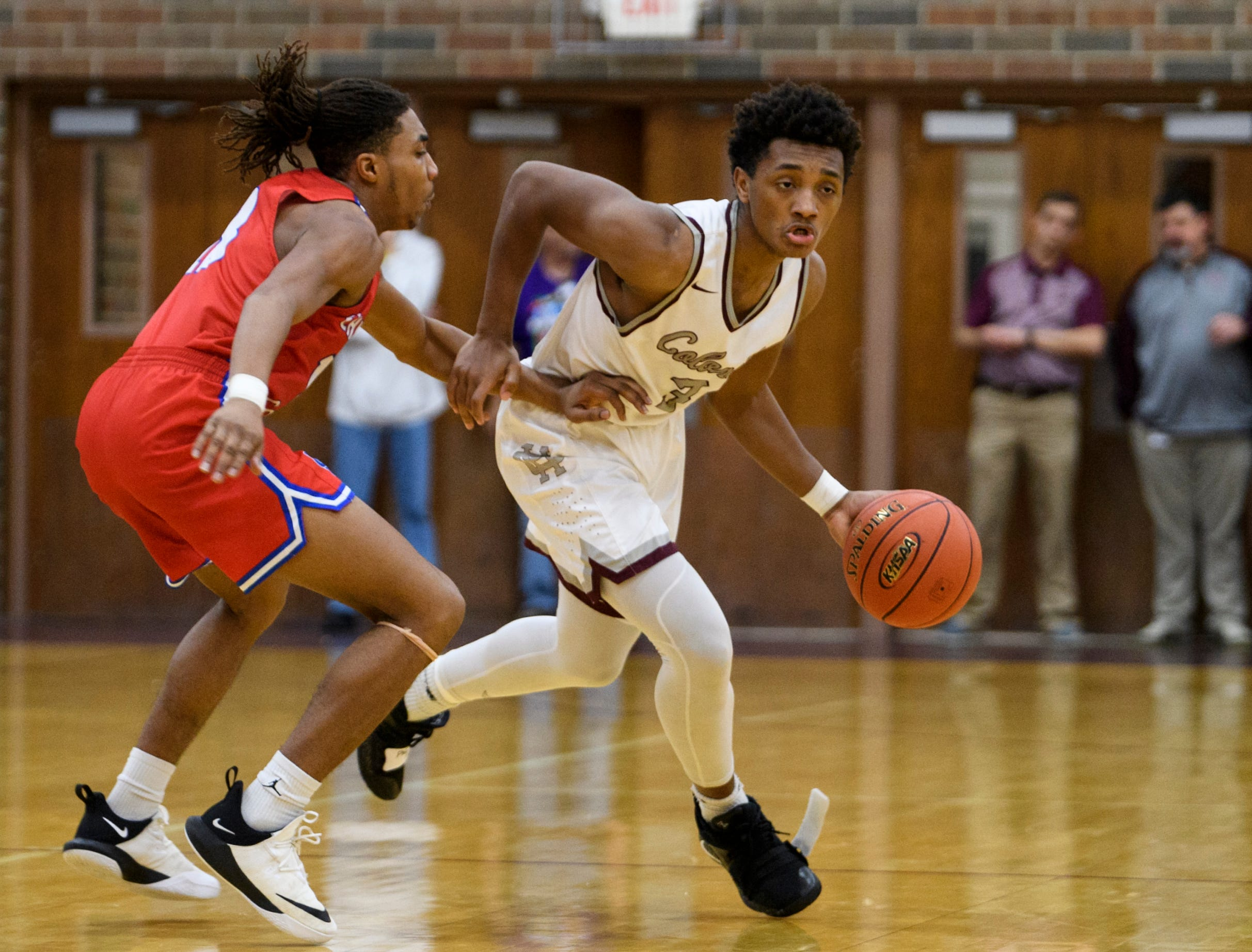 Henderson's Daymian Dixon (3) dribbles around Christian County's Eric Brody (13) during the second quarter at Henderson County High School in Henderson, Ky., Friday, Dec. 14, 2018. Christian County defeated Henderson County 79-71.