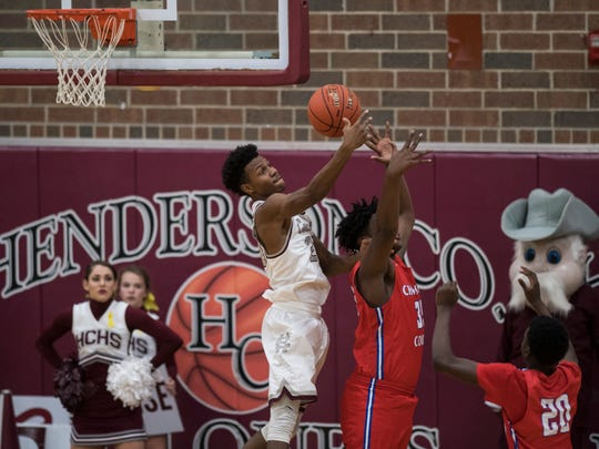 Henderson's Myekel Sanners (23) knocks the ball away from Christian County's Olajuwon White (35) as they fight for the rebound during the fourth quarter at Henderson County High School in Henderson, Ky., Friday, Dec. 14, 2018.Christian County defeated Henderson County 79-71.