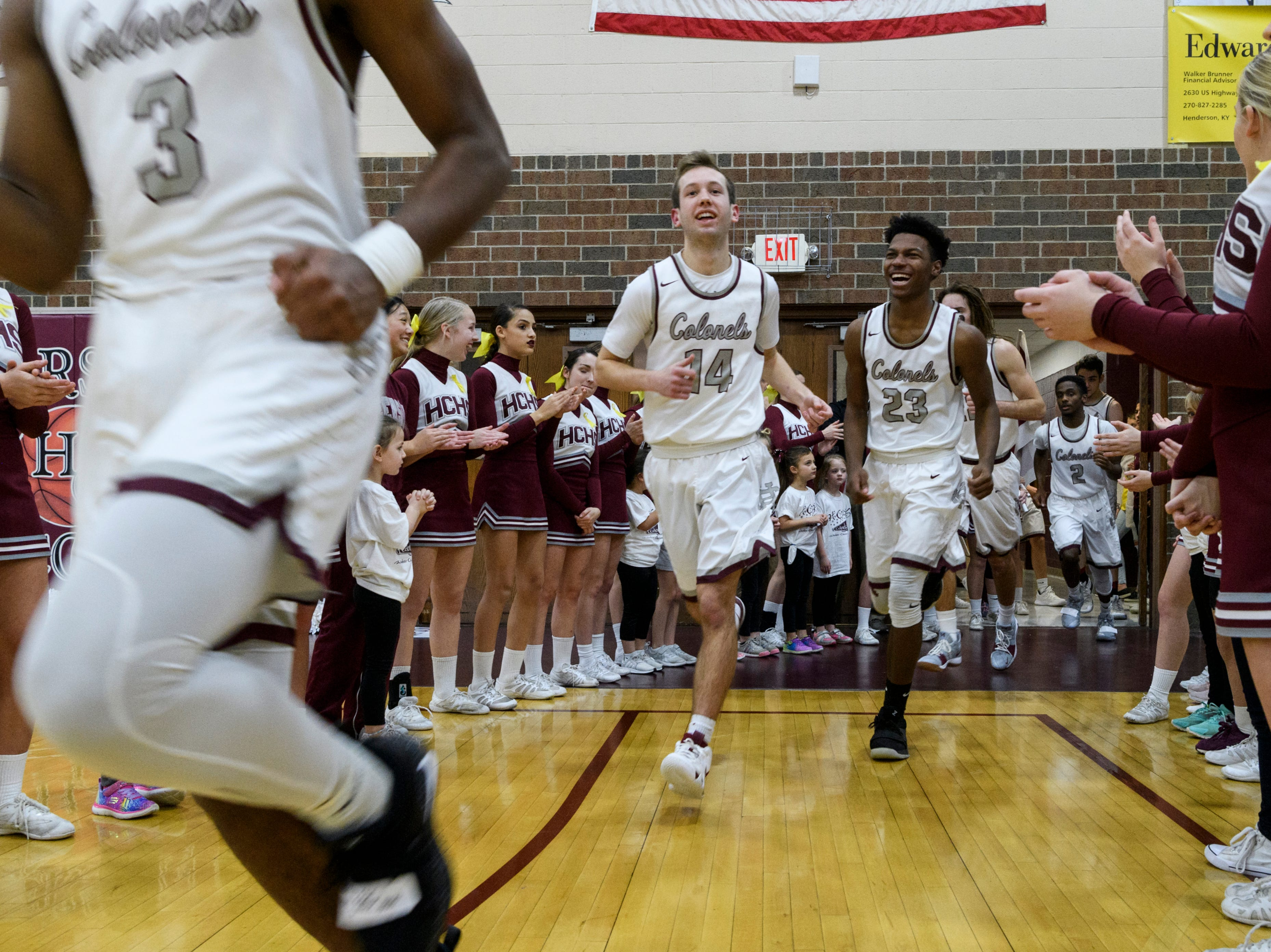 Henderson's Daymian Dixon (3), Holden Raley (14), Myekel Sanners (23) and the rest of the team rush the court before the start of the game against the Christian County Colonels at Henderson County High School in Henderson, Ky., Friday, Dec. 14, 2018. Christian County defeated Henderson County 79-71.