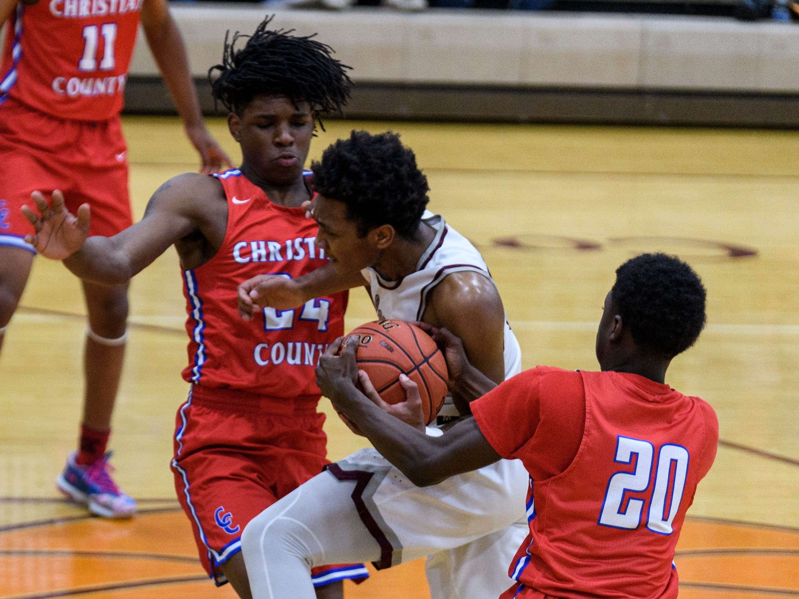 Christian County's Stephen Bussell (24) assists Christian County's Marquadion Chambers (20) as he steals the ball from Henderson's Daymian Dixon (3) during the first quarter at Henderson County High School in Henderson, Ky., Friday, Dec. 14, 2018. Christian County defeated Henderson County 79-71.