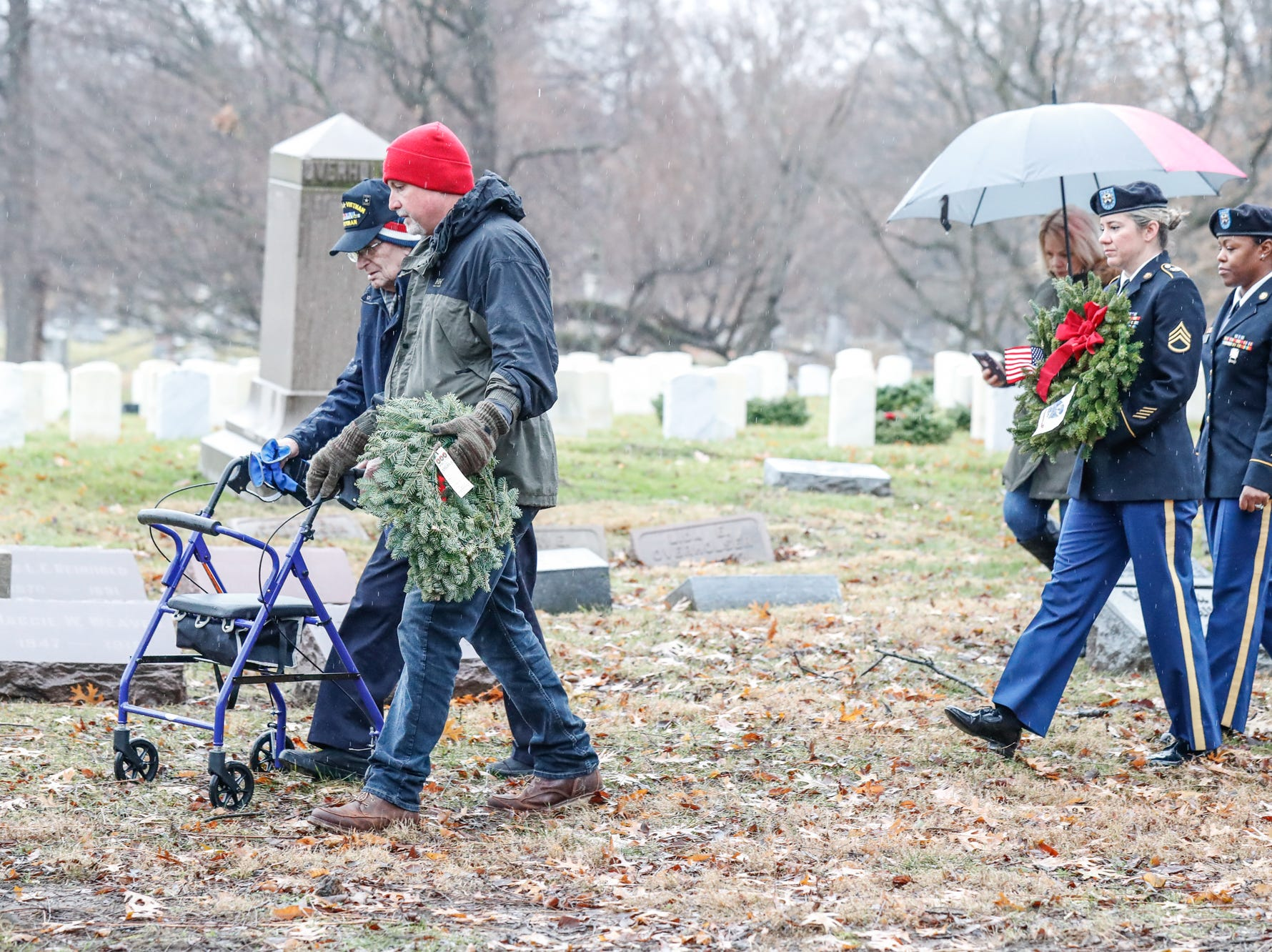 Bruce Bowman, front right, and Retired Sargent First Class, Bill Pridemore, front left, lay wreaths during the Wreaths Across America ceremony in remembrance of fallen military heroes at Crown Hill Cemetery on Saturday, Dec. 2018.