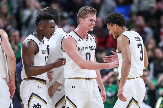 Notre Dame Fighting Irish TJ Gibbs (10), Rex Pflueger (0) and Prentiss Hubb (3) celebrate the team's lead in the first half of the Crossroads Classic game between Purdue and Notre Dame at Banker's Life Fieldhouse in Indianapolis, Saturday, Dec. 15, 2018.