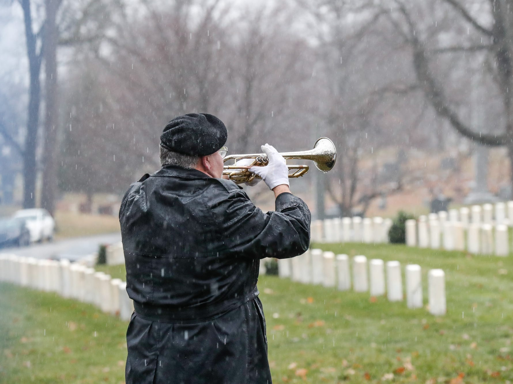 Military veteran Bruce McKee plays Taps during the Wreaths Across America wreath laying in remembrance of fallen military heroes at Crown Hill Cemetery on Saturday, Dec. 2018.