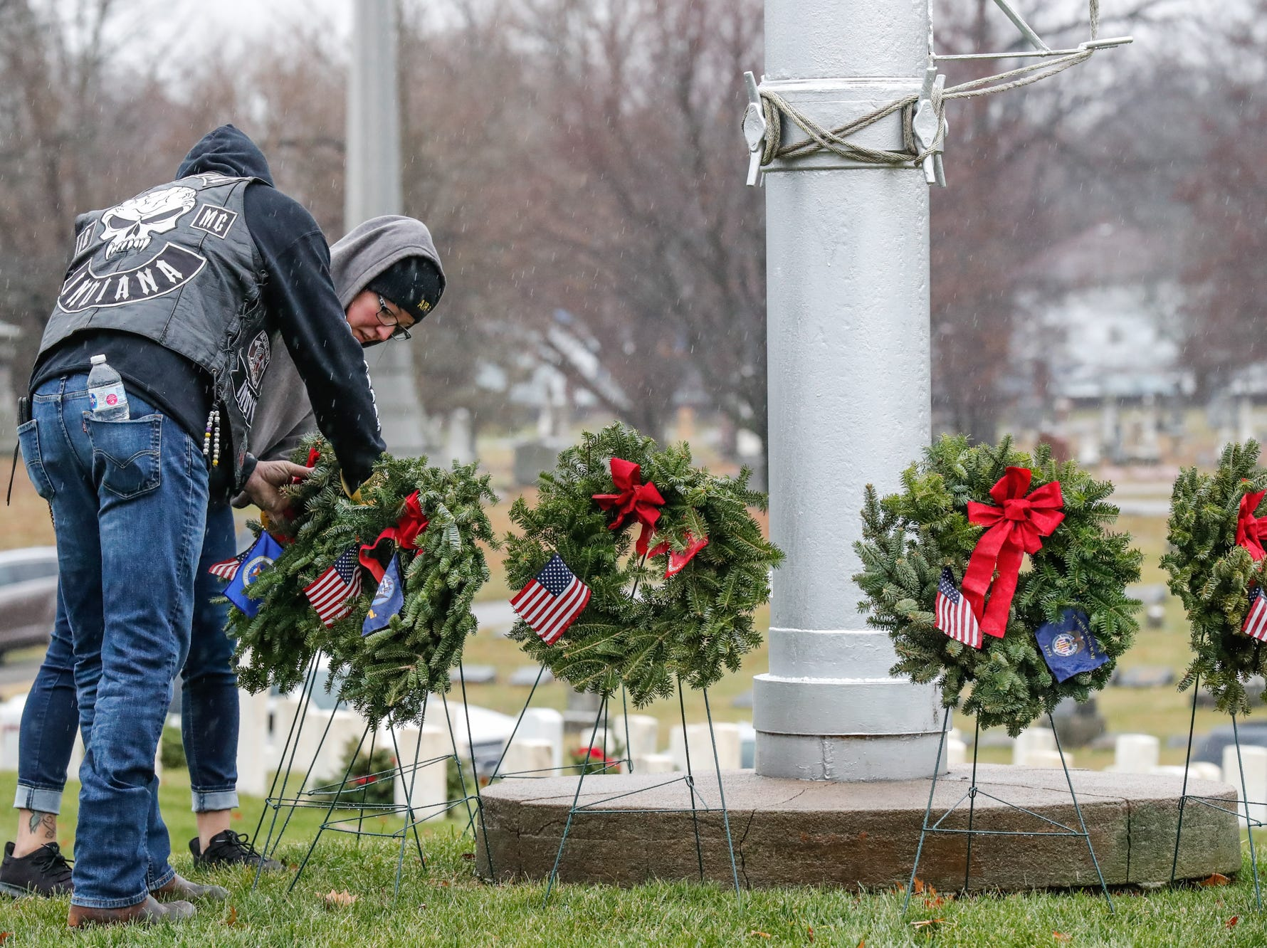 Active duty military members John and Amber Stark lay wreath during the Wreaths Across America wreath laying in remembrance of fallen military heroes at Crown Hill Cemetery on Saturday, Dec. 2018.