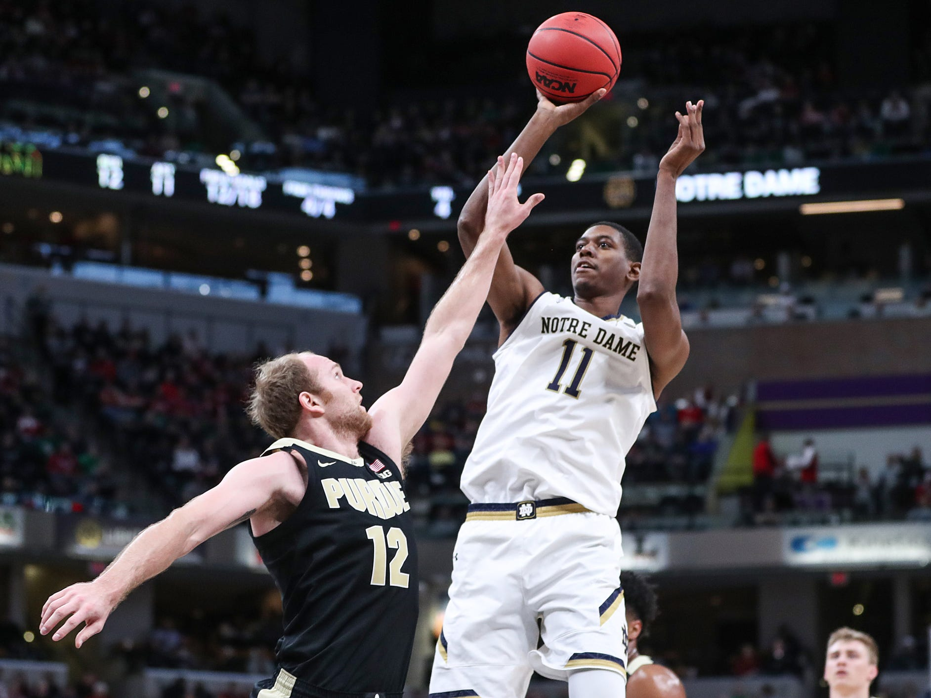 Purdue Boilermakers forward Evan Boudreaux (12) tries to block a shot by Notre Dame Fighting Irish forward Juwan Durham (11) in the first half of the Crossroads Classic game between Purdue and Notre Dame at Banker's Life Fieldhouse in Indianapolis, Saturday, Dec. 15, 2018.