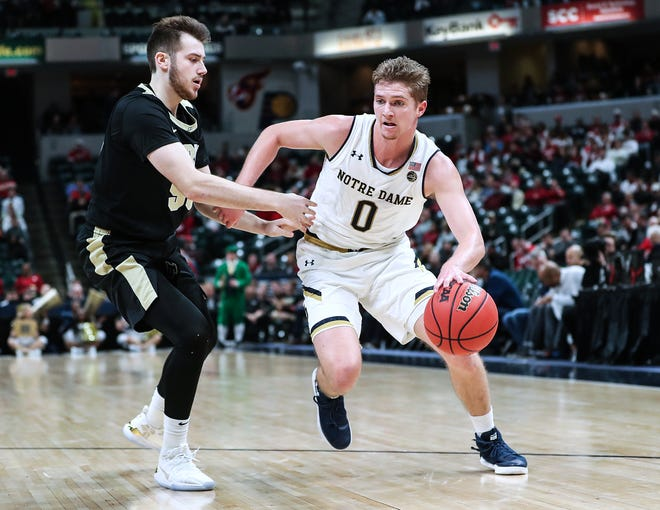 Purdue Boilermakers guard Sasha Stefanovic (55) guards Notre Dame Fighting Irish guard Rex Pflueger (0) as he works a possession in the first half of the Crossroads Classic game between Purdue and Notre Dame at Banker's Life Fieldhouse in Indianapolis, Saturday, Dec. 15, 2018.