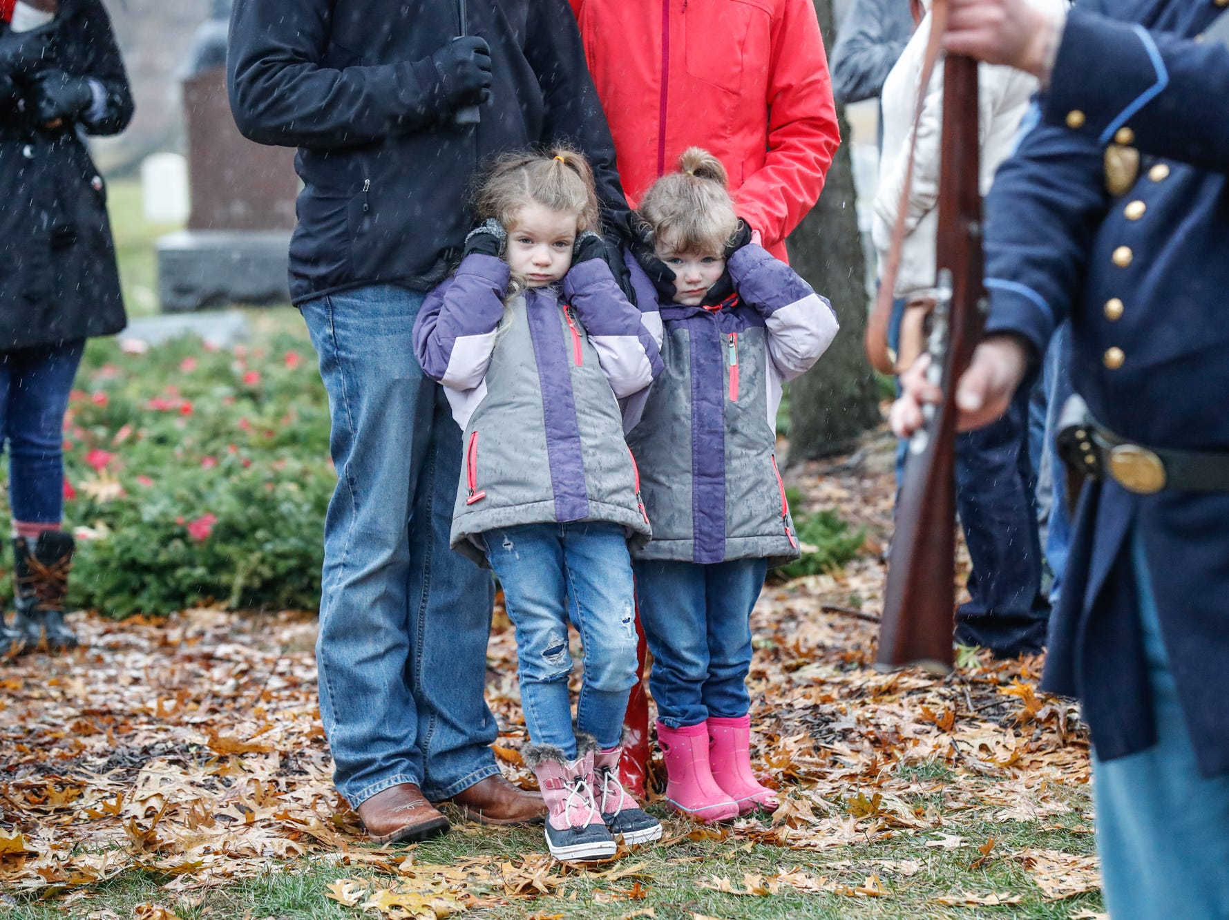 Charlotte and Bailey Pegram cover their ears for the twenty one gun salute during the Wreaths Across America wreath laying in remembrance of fallen military heroes at Crown Hill Cemetery on Saturday, Dec. 2018.