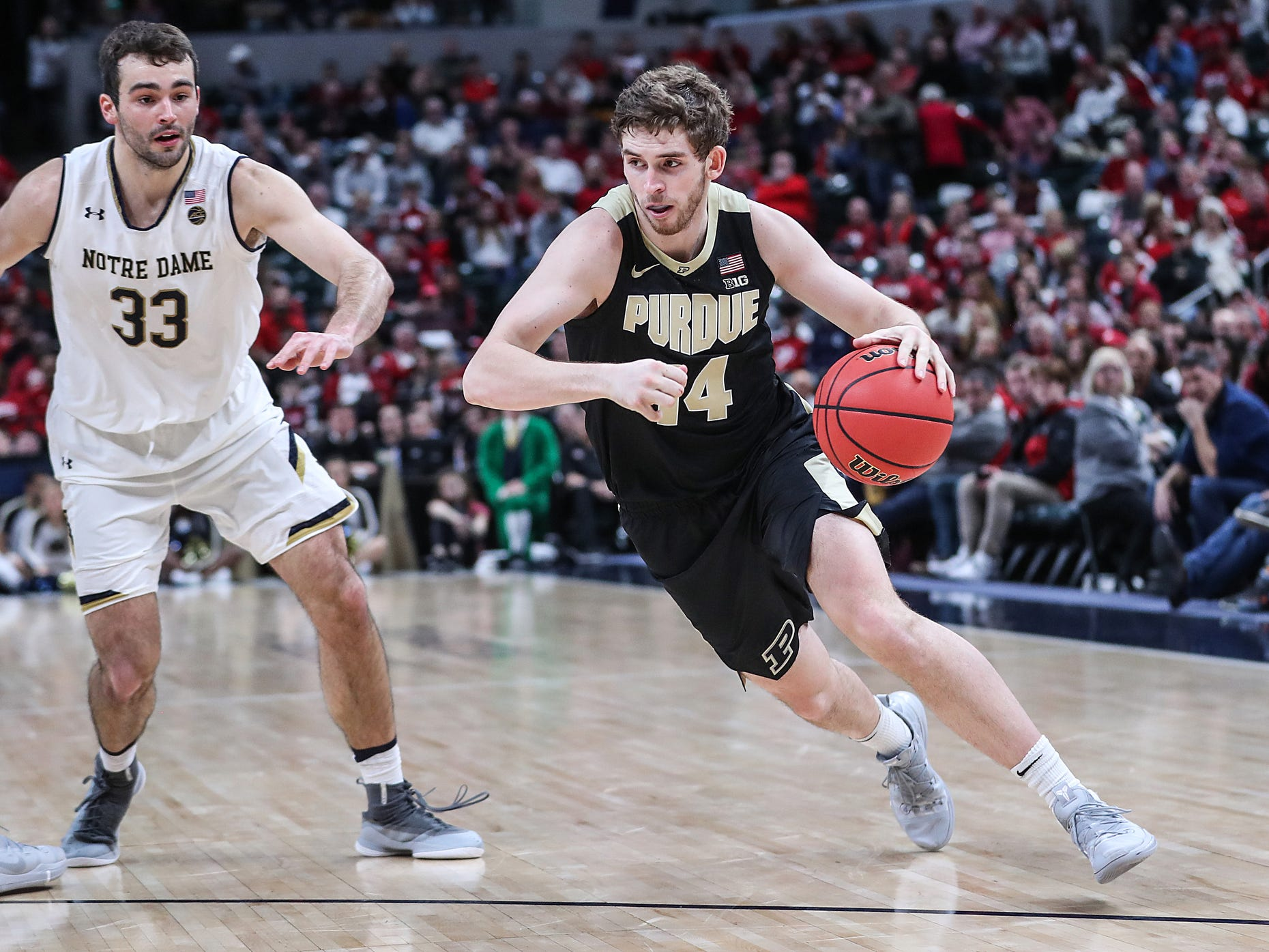 Notre Dame Fighting Irish forward John Mooney (33) guards Purdue Boilermakers guard Ryan Cline (14) as he drives toward the basket in the second half of the Crossroads Classic game between Purdue and Notre Dame at Bankers Life Fieldhouse in Indiananpolis, Saturday, Dec. 15, 2018. Notre Dame won, 88-80.