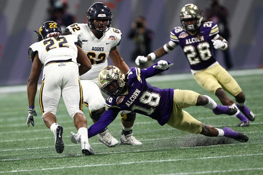 Alcorn State's Leishaun Ealey (18) dives at the legs of North Carolina A&T's Marquell Cartwright (22) during Saturday's Celebration Bowl game in Atlanta, Georgia.