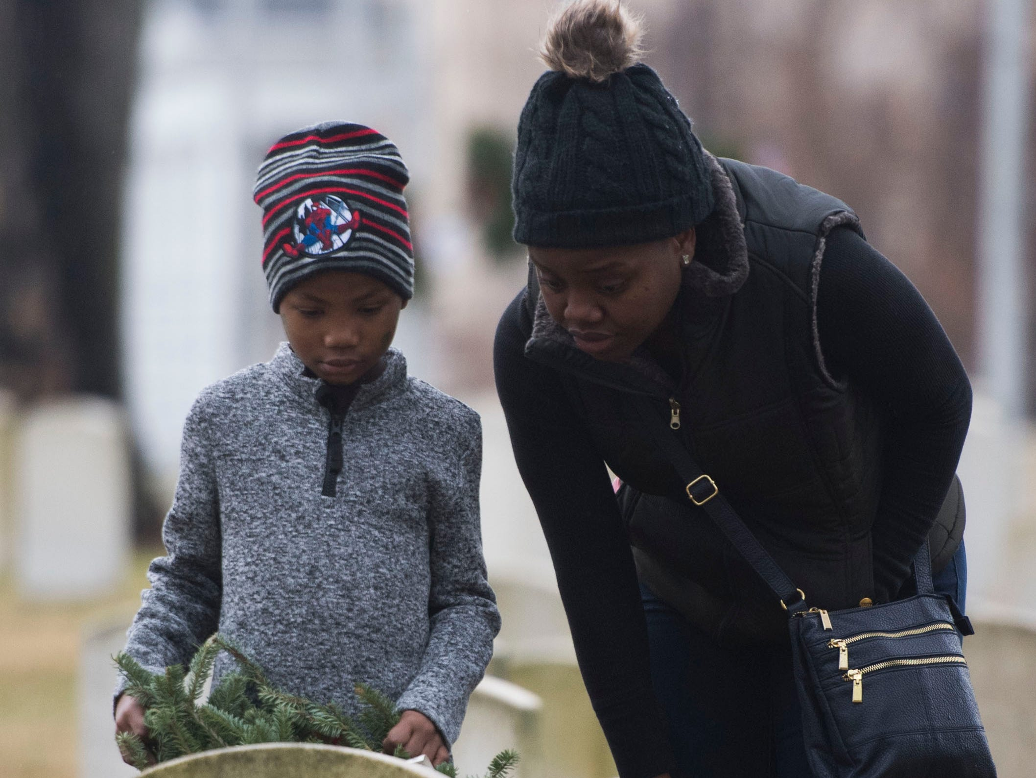Lordensky, 8, and his mother Melissa Fifi, of Knoxville, place a wreath on a headstone during a Wreaths Across America ceremony at Knoxville National Cemetery north of downtown Knoxville Saturday, Dec. 15, 2018.