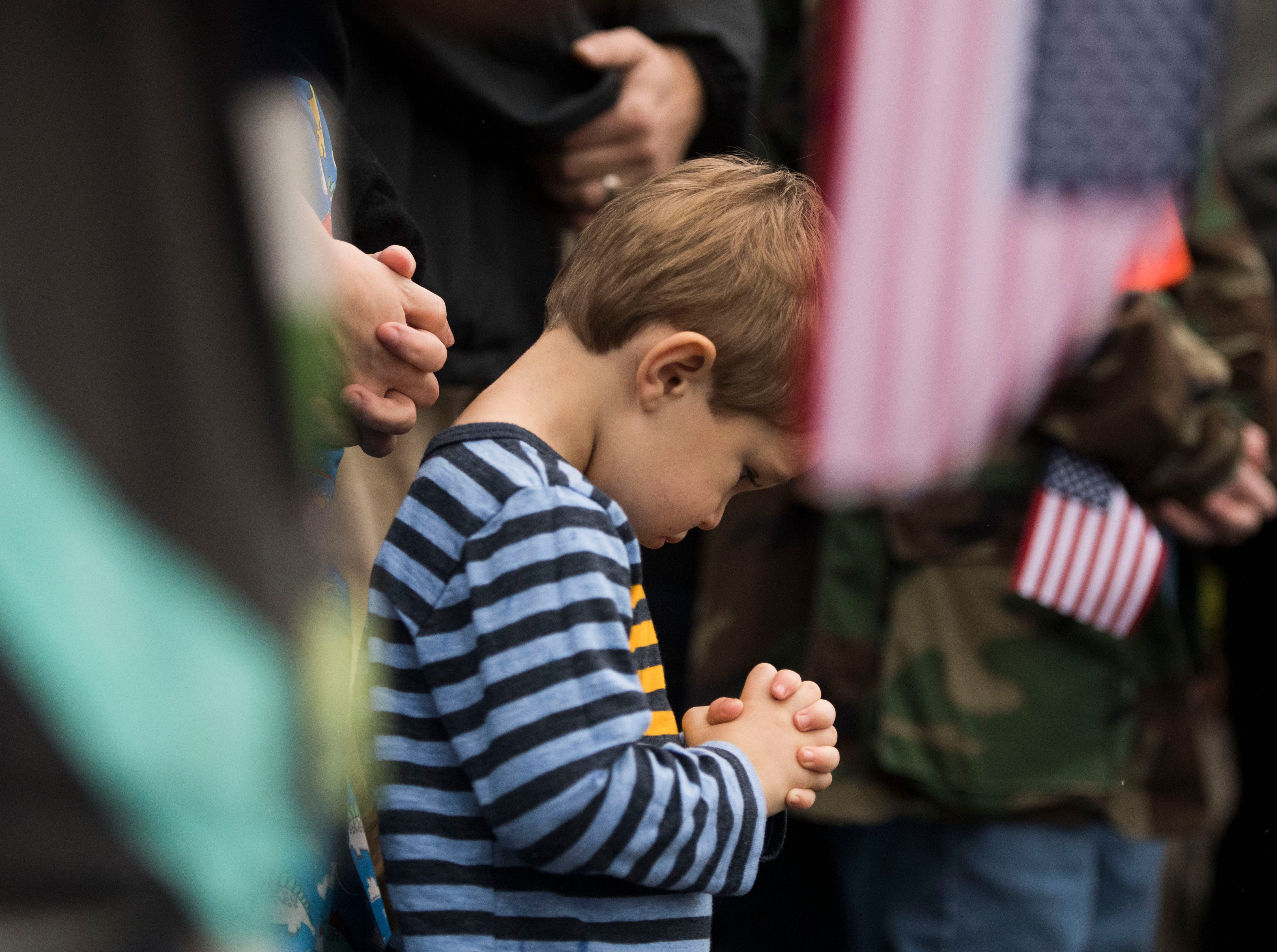Lincoln Walker, 3, bows his head for a prayer during a Wreaths Across America ceremony at Knoxville National Cemetery north of downtown Knoxville Saturday, Dec. 15, 2018. Evergreen wreaths were placed on veteran headstones.