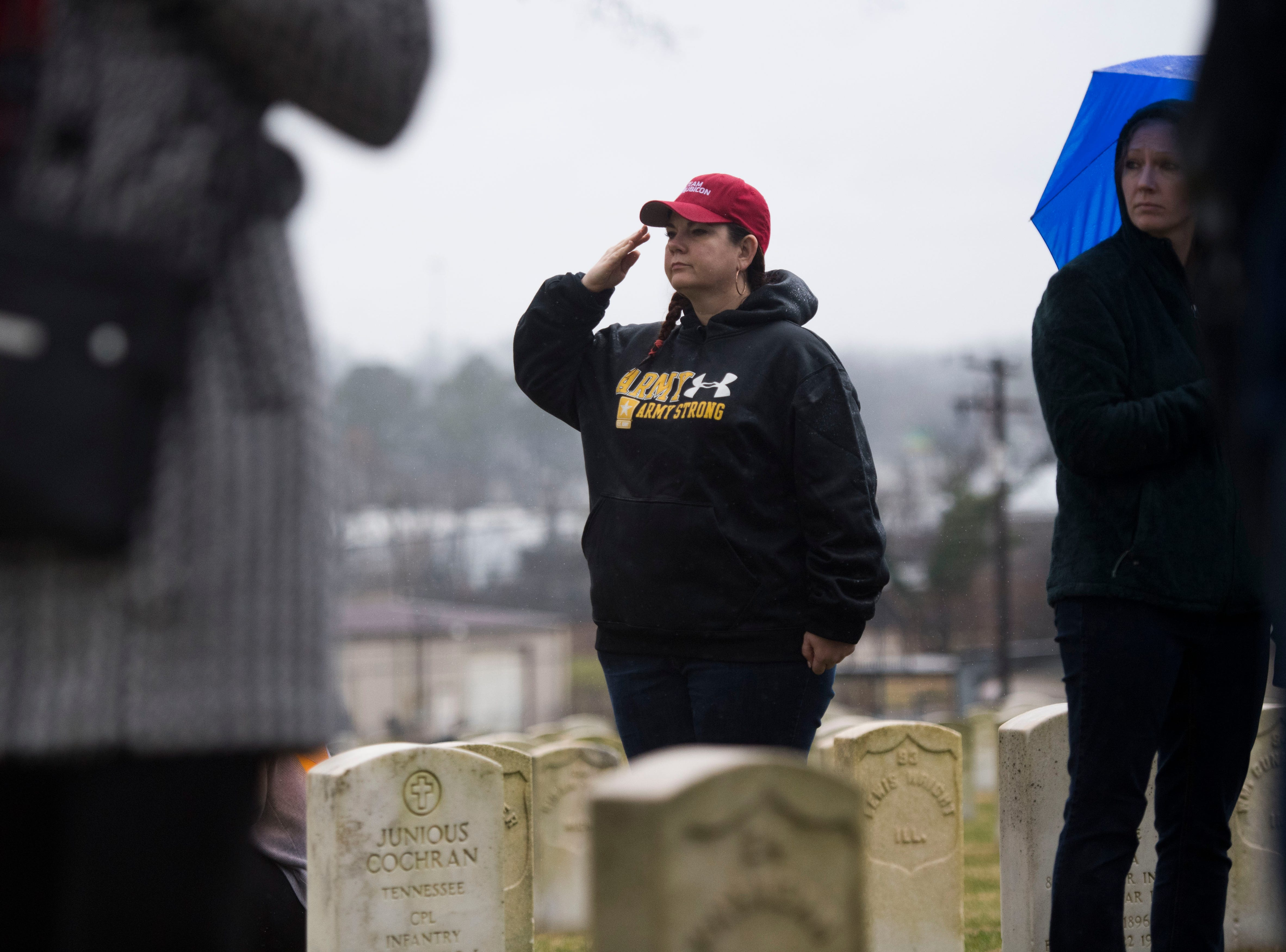 An attendee salutes during a Wreaths Across America ceremony at Knoxville National Cemetery north of downtown Knoxville Saturday, Dec. 15, 2018. Evergreen wreaths were placed on veteran headstones.
