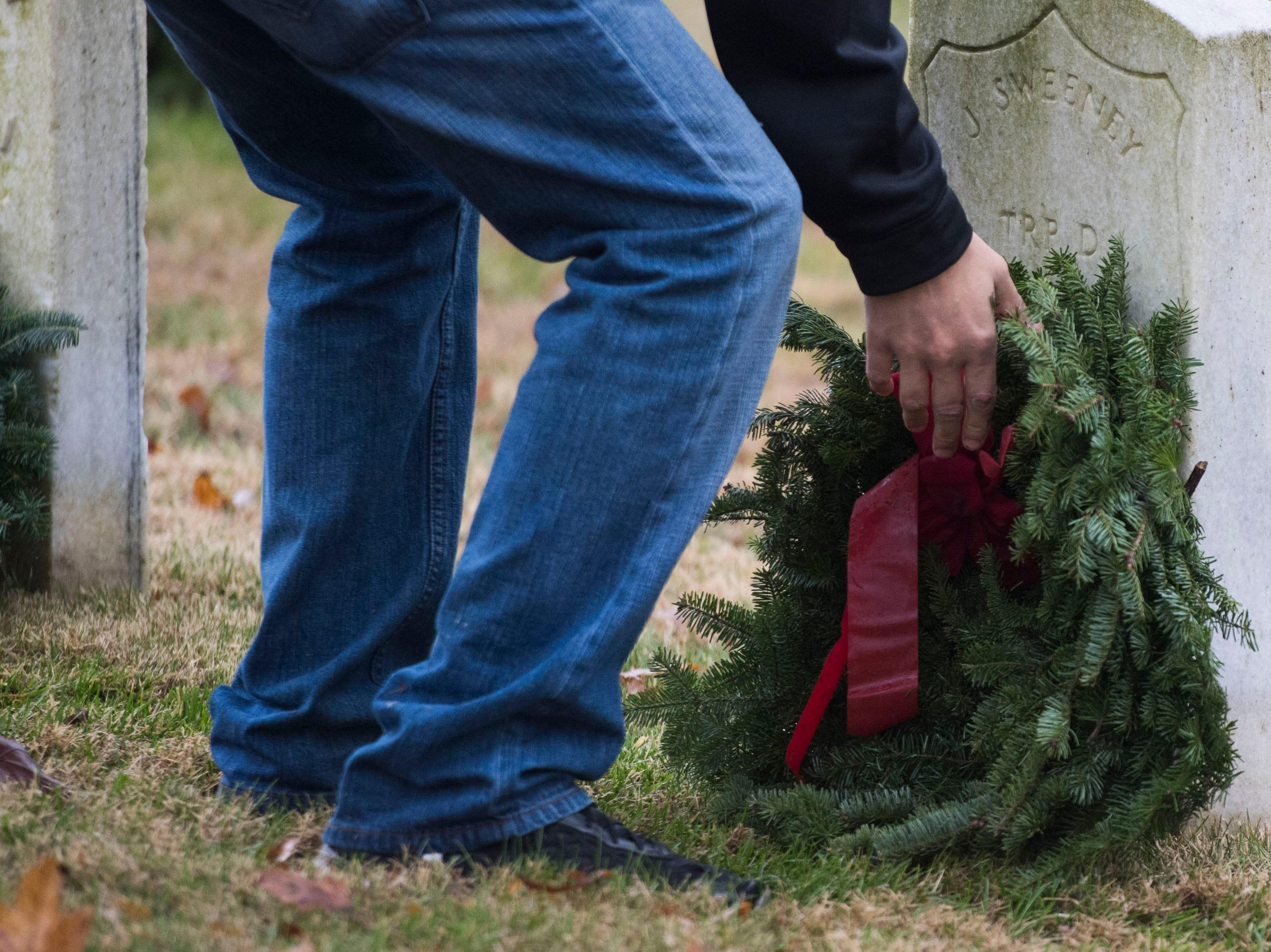 Wreaths are placed on headstones during a Wreaths Across America ceremony at Knoxville National Cemetery north of downtown Knoxville Saturday, Dec. 15, 2018. Evergreen wreaths were placed on veteran headstones.