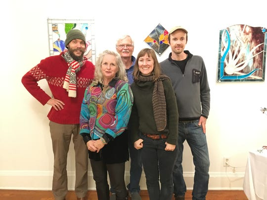 Evan Tishuk, Susan Watson Arbital, Bill Murrah, Erin Bicknese and Bryan Alexander celebrate the window installation at a reception for the neighborhood at The Birdhouse on Friday, Dec. 14. They're shown with some of Arbital's original pieces.