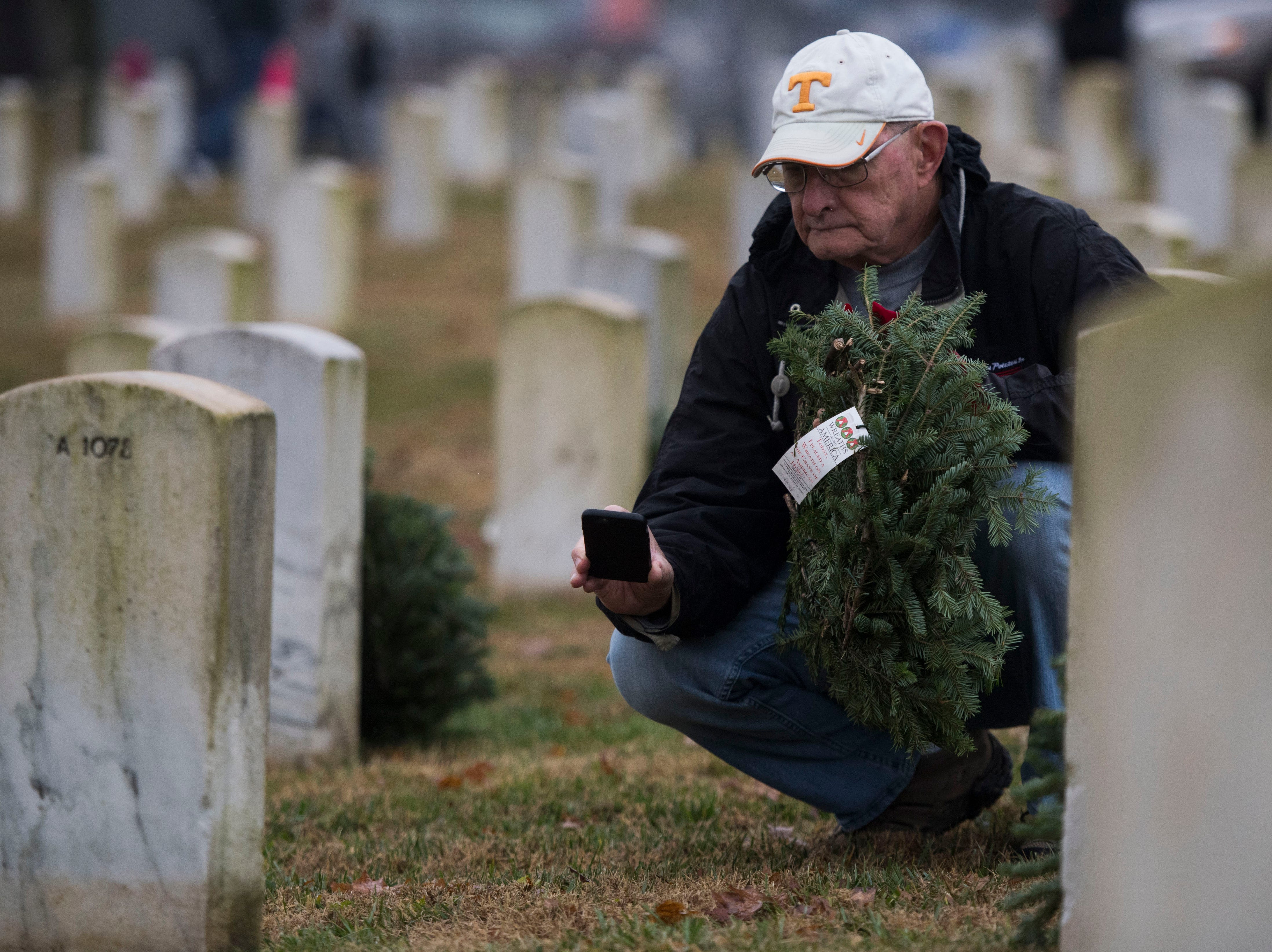 Dennis Flynn of Crossville looks at a grave before placing a wreath on it during a Wreaths Across America ceremony at Knoxville National Cemetery north of downtown Knoxville Saturday, Dec. 15, 2018.