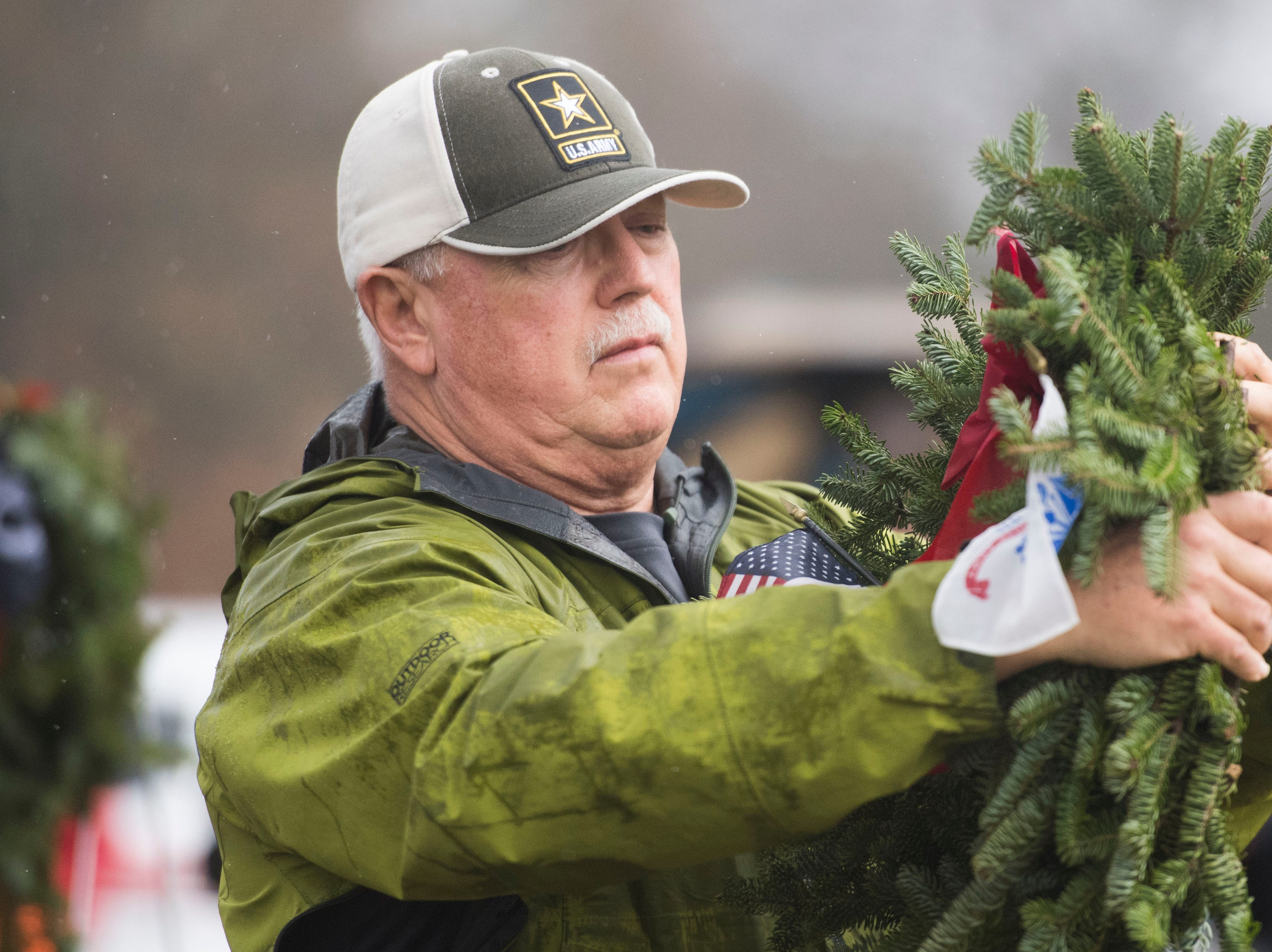 Army veteran Dan Davis places a wreath on a stand during a Wreaths Across America ceremony at Knoxville National Cemetery north of downtown Knoxville Saturday, Dec. 15, 2018. Evergreen wreaths were placed on veteran headstones.