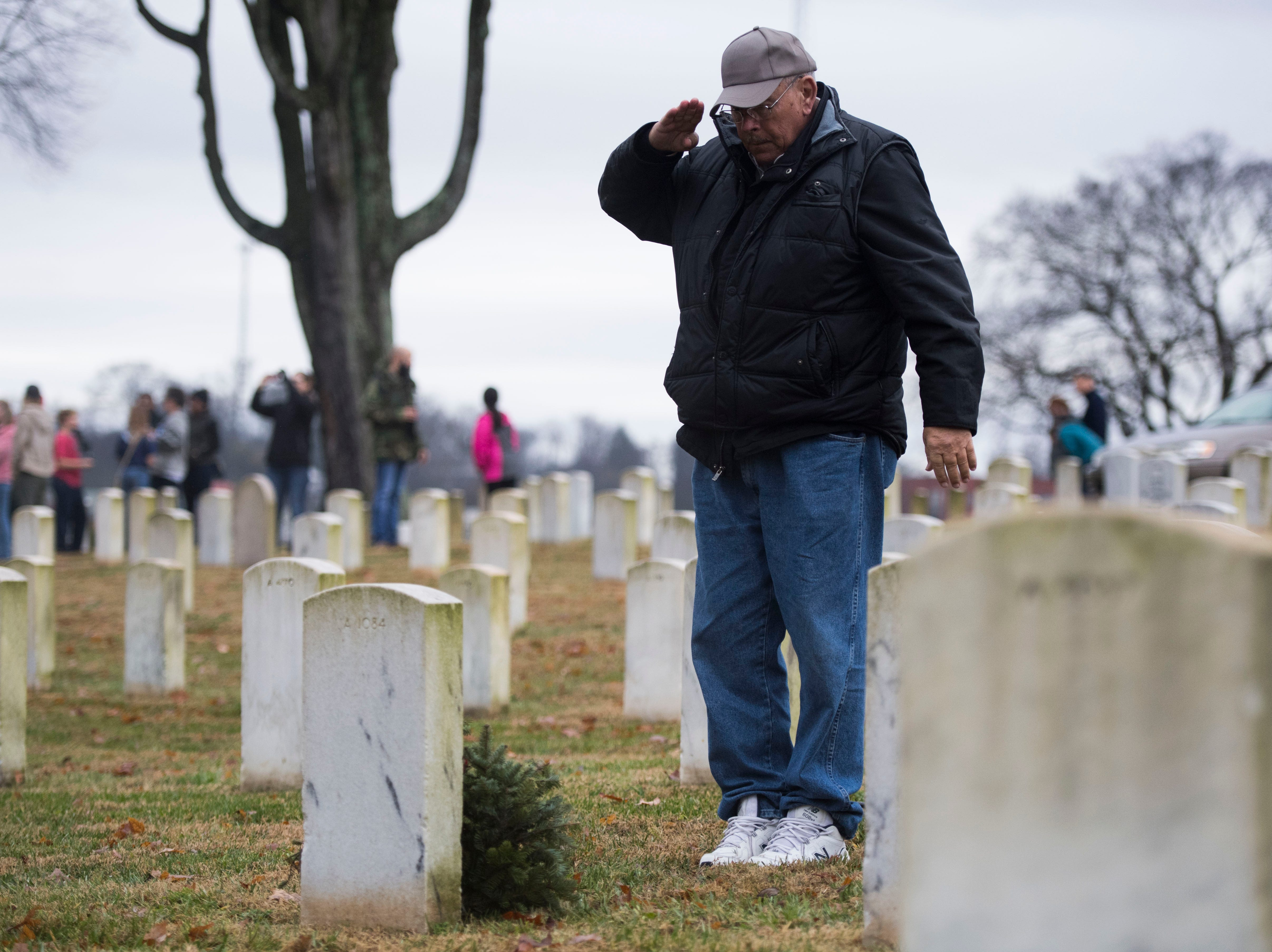 David Bounds of Athens, who retired from the Air National Guard, salutes a headstone during a Wreaths Across America ceremony at Knoxville National Cemetery north of downtown Knoxville Saturday, Dec. 15, 2018. Evergreen wreaths were placed on veteran headstones.