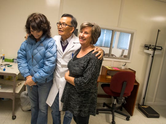 Dr. Tom Kim, center, embraces volunteer nurse Janet Master, left, and volunteer secretary Linda Scott, before the three closed down the free medical clinic at Abner Ross Memorial Center in Deer Lodge on Dec. 14.