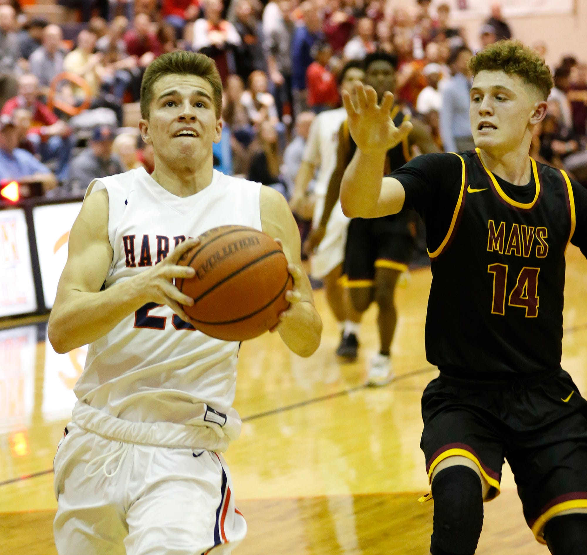 Clayton Burgh of Harrison with a drive to the basket against Rowen Farrell of McCutcheon Friday, December 14, 2018, in West Lafayette. Harrison defeated county rival McCutcheon 40-26.