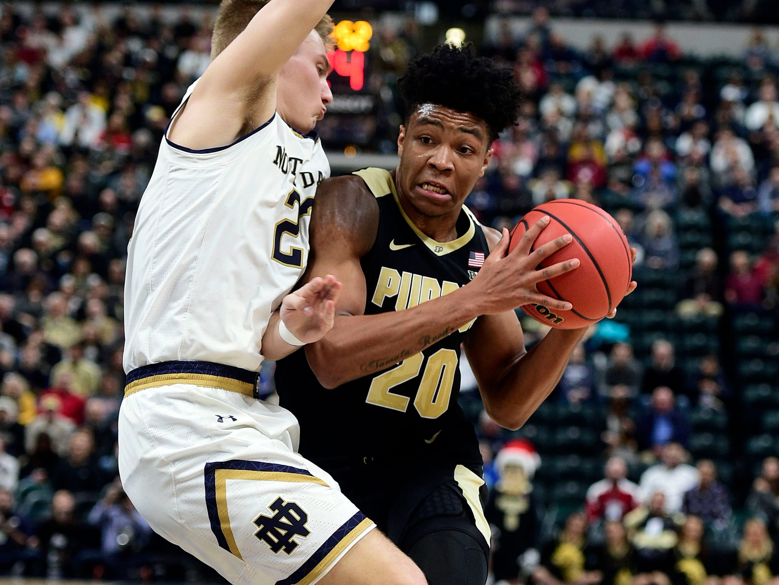 Dec 15, 2018; Indianapolis, IN, USA; Purdue Boilermaker guard Nojel Eastern (20) drives past Notre Dame Fighting Irish guard Liam Nelligan (25) in the first half at Bankers Life Fieldhouse. Mandatory Credit: Thomas J. Russo-USA TODAY Sports