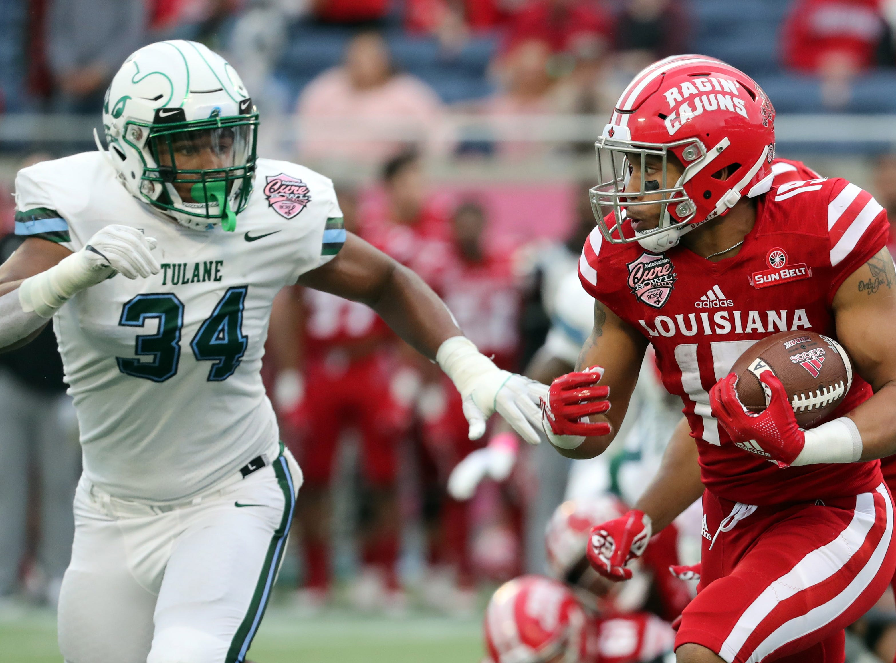 Dec 15, 2018; Orlando, FL, USA; Louisiana-Lafayette Ragin Cajuns running back Elijah Mitchell (15) runs with the ball as Tulane Green Wave defensive end Patrick Johnson (34) defends during the first half at Camping World Stadium. Mandatory Credit: Kim Klement-USA TODAY Sports