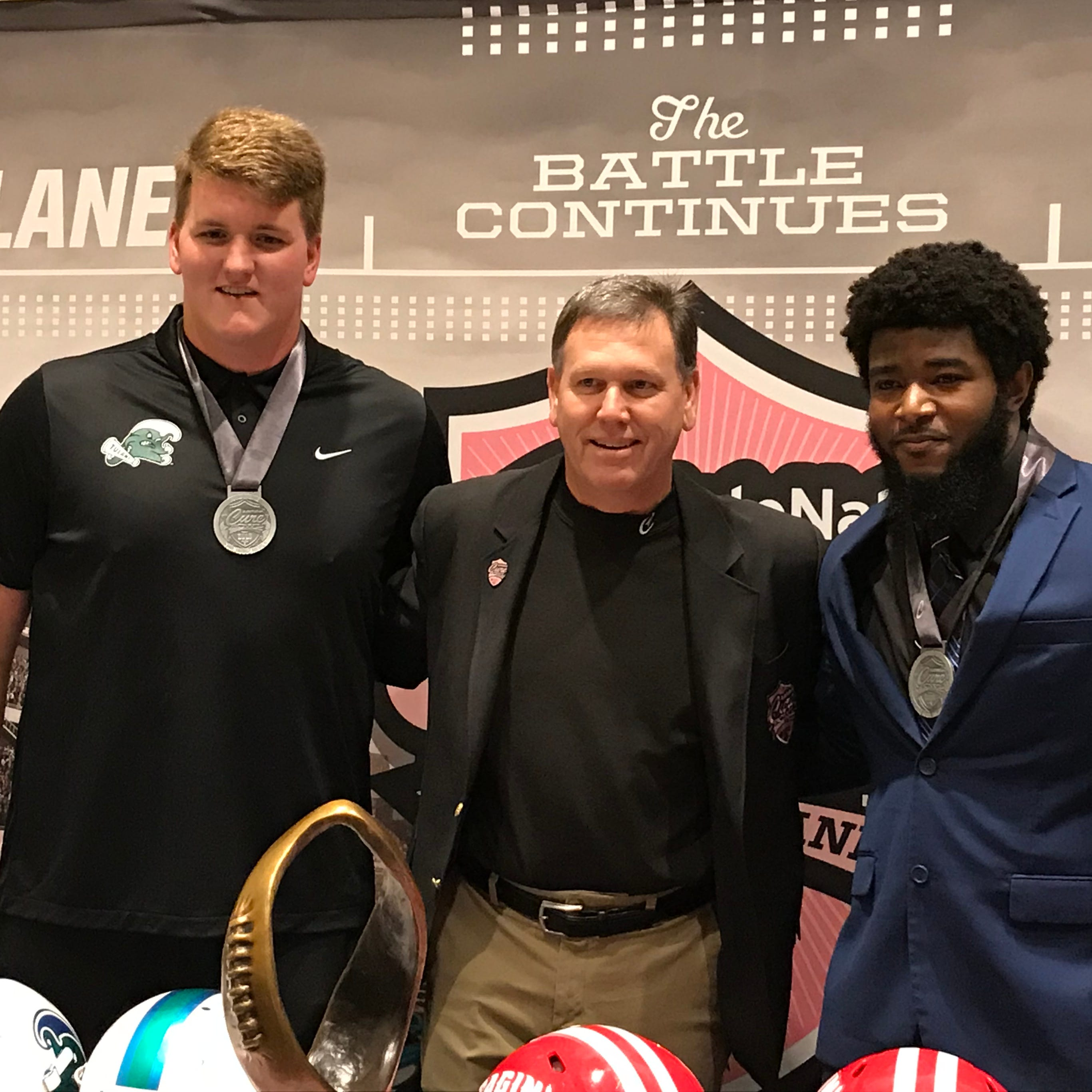 Tulane offensive lineman John Leglue, left, and UL linebacker Alonzo Brown, right, were awarded medals for exemplary community service by Cure Bowl executive director Alan Gooch, middle.