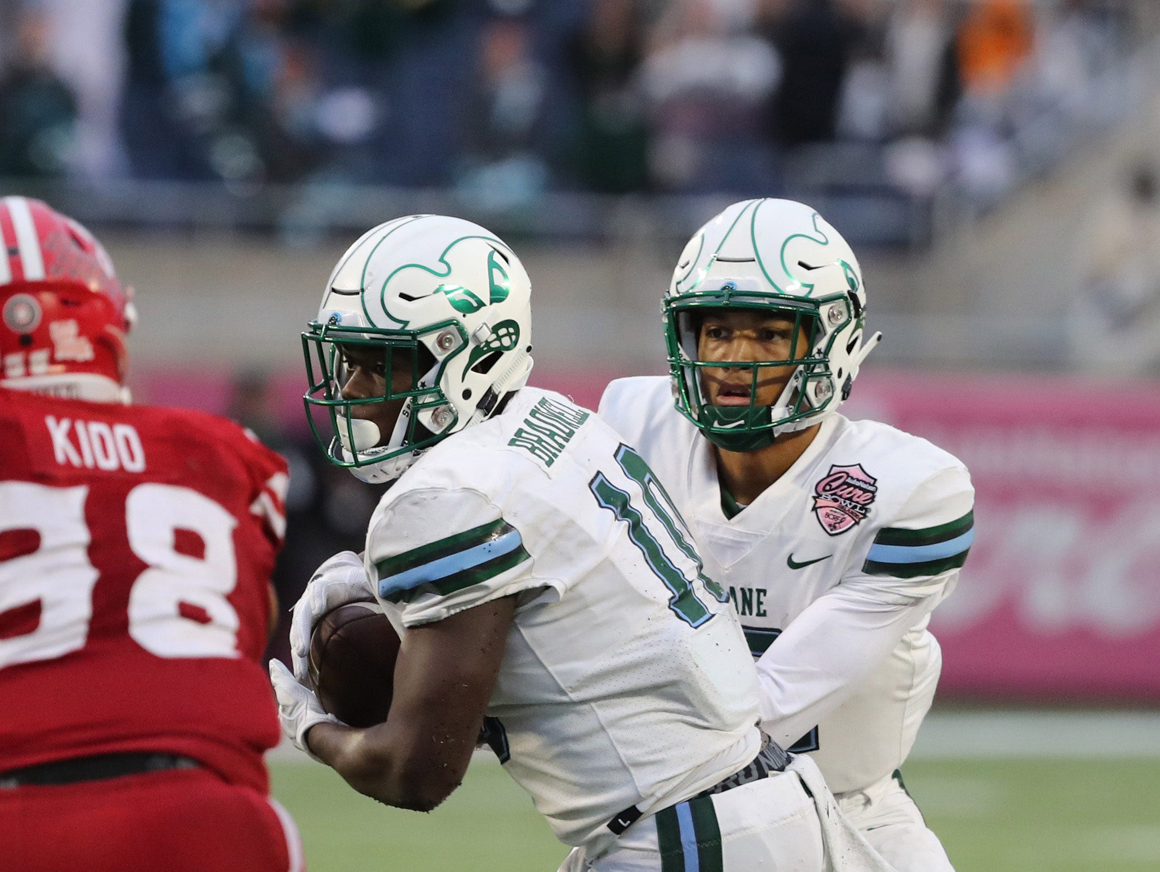 Dec 15, 2018; Orlando, FL, USA; Tulane Green Wave quarterback Justin McMillan (12) hands the ball off to Tulane Green Wave running back Darius Bradwell (10)  against the Louisiana-Lafayette Ragin Cajuns during the second half at Camping World Stadium. Mandatory Credit: Kim Klement-USA TODAY Sports