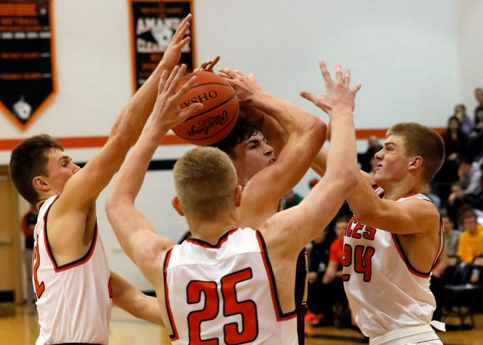 Bloom-Carroll's Otto Kuhnis swarmed by Amanda-Cleracreek's Andrew Hunter, left, Jesse Connell, center, and Jayse Miller, right, Friday night, Dec. 14, 2018, at Amanda-Clearcreek High School in Amanda. The Aces won the game 47-39.