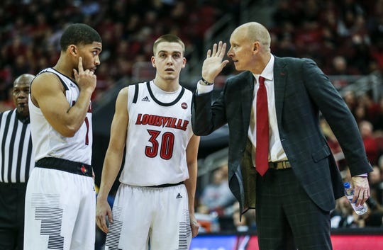 Christen Cunningham (left) and Ryan McMahon (center) listen to Louisville coach Chris Mack during the game against Kent State.