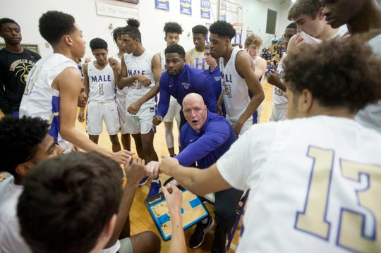 Male head basketball coach Timothy D. Haworth joins hands with his team toward the end of a time-out.