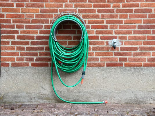 Green Garden Water Hose Mounted On Red Brickwall