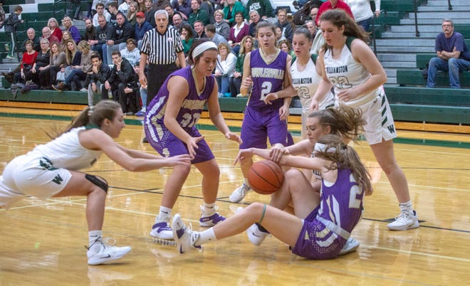 Fowlerville and Williamston basketball players scramble for a loose ball during their game on Friday, Dec. 14, 2018.